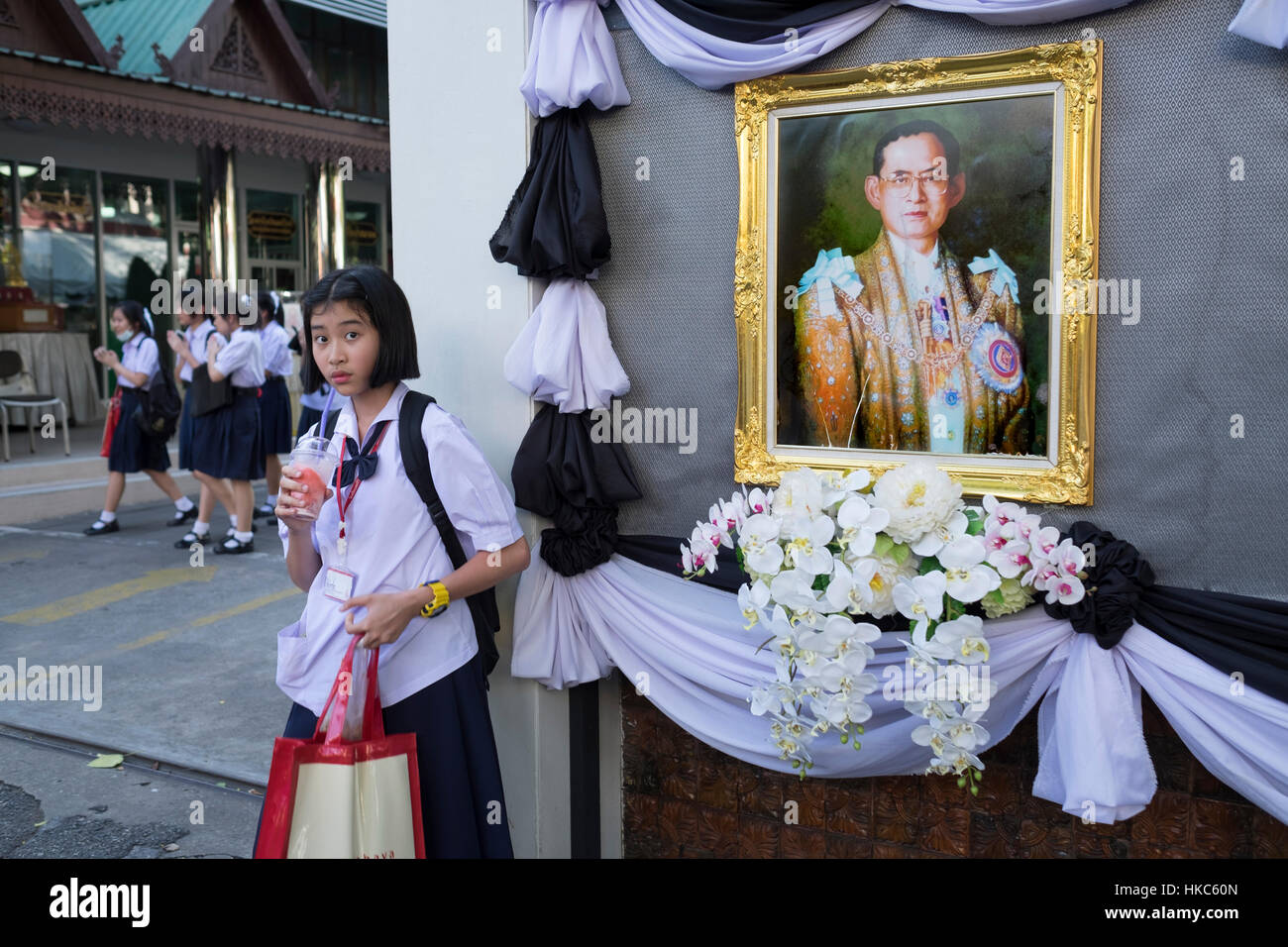 Thai School Girl Is Seen Next To A Portrait Of King Bhumibol Adulyadej Stock Image