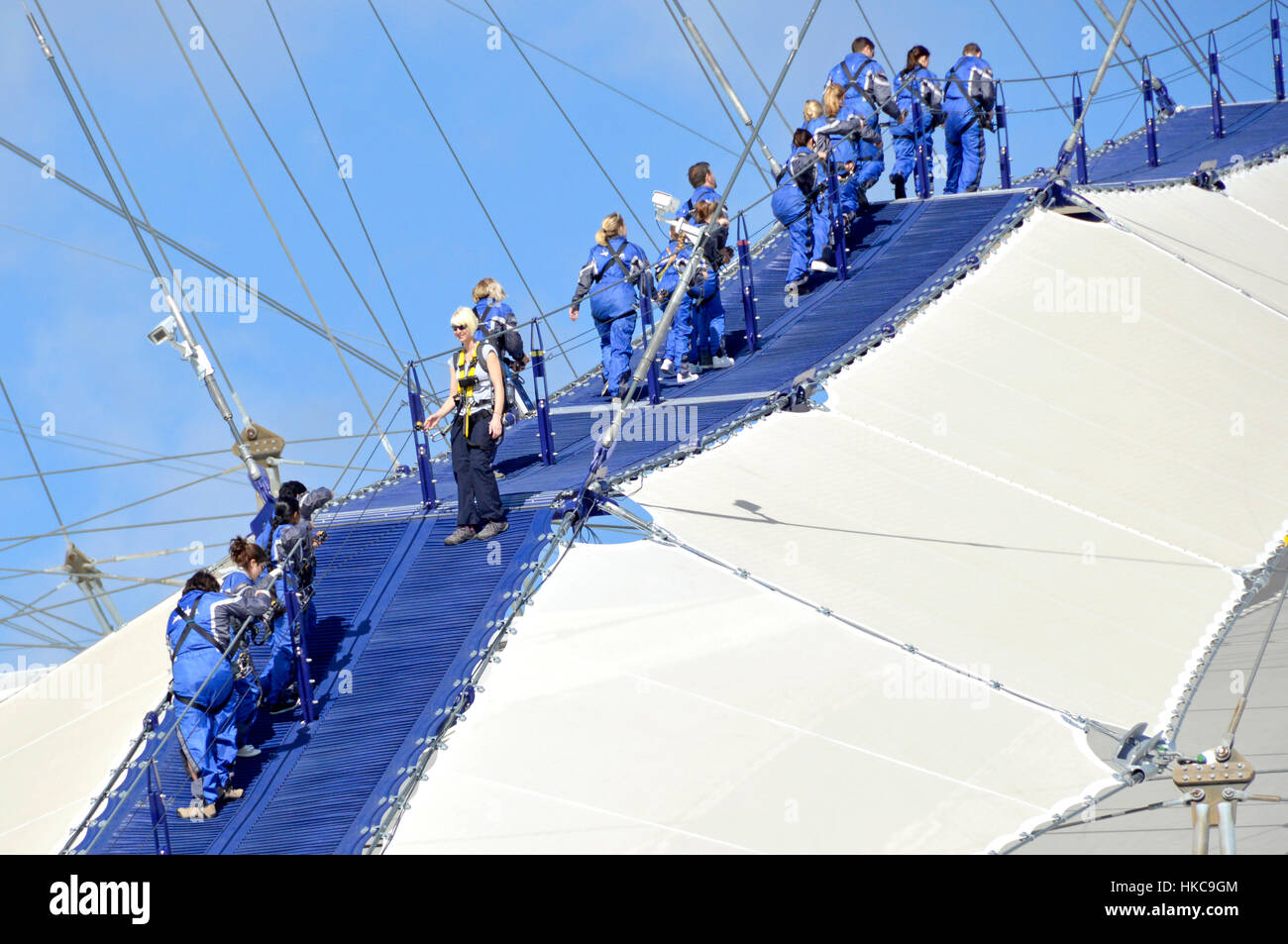 Up At The O2, O2 millenium arena London England millennium dome rooftop walk Skywalk people wearing blue overalls - Stock Image