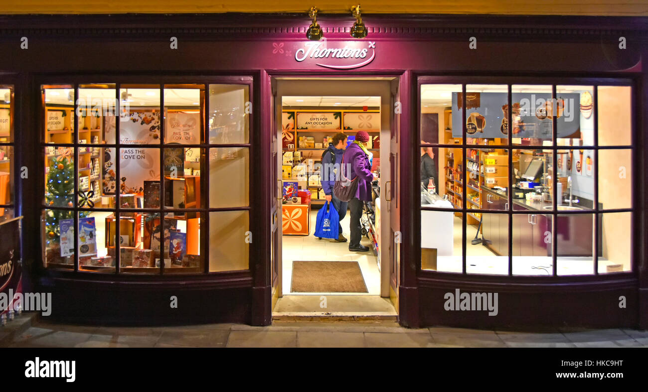 Customers winter afternoon shopping in a Scottish Thorntons retail chocolate shop bow fronted windows open door - Stock Image