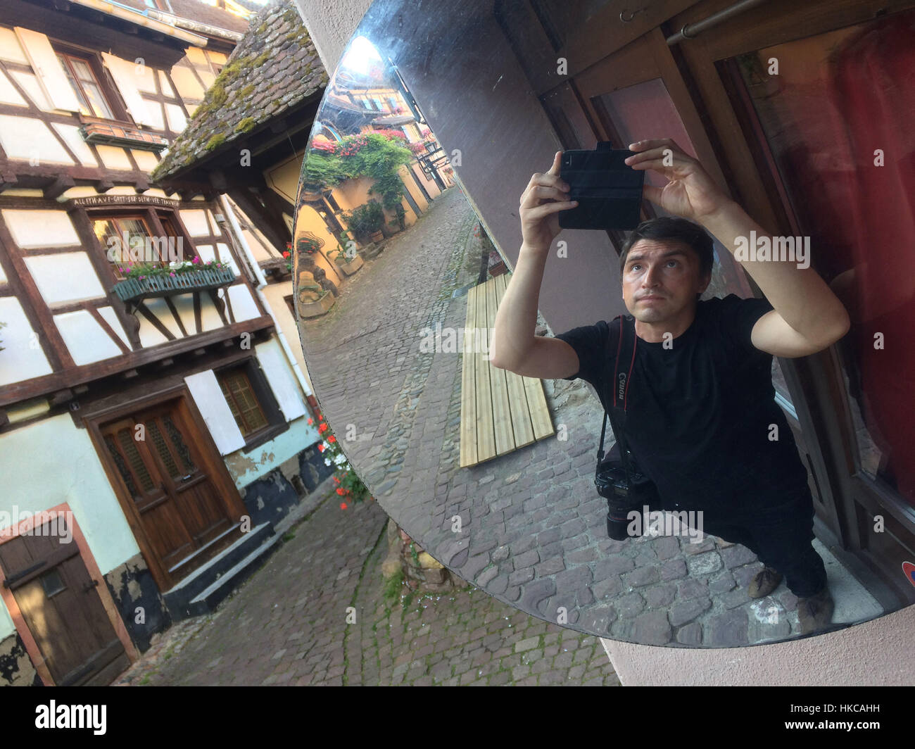 Photographer Vova Pomortzeff uses a smartphone to make a selfie using a convex mirror in Eguisheim, Alsace, France. Stock Photo