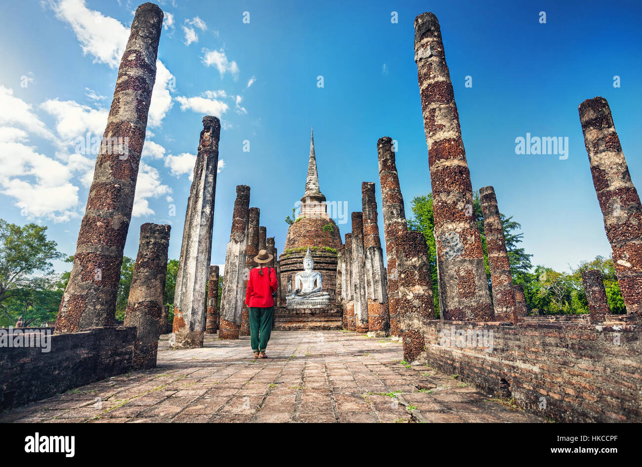 Tourist Woman in red costume looking at ancient Buddha statue in Wat Sa Si of Sukhothai Historical Park, Thailand - Stock Image