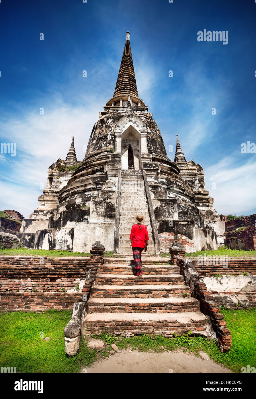 Tourist Woman in red costume looking at ancient ruined stupa in Ayutthaya Historical Park, Thailand - Stock Image