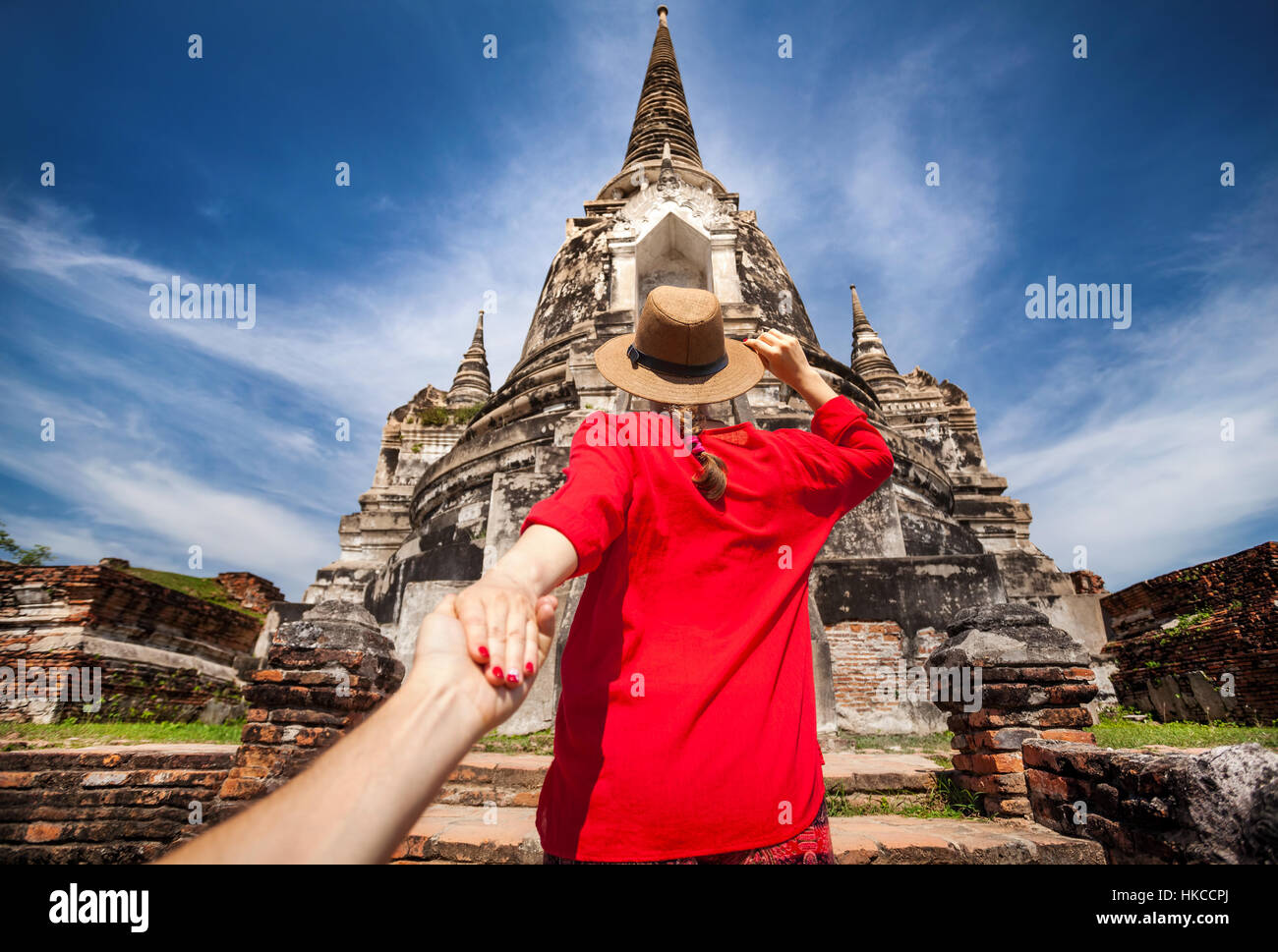 Tourist Woman in red shirt holding her husband by hand and going to ancient stupa in Ayutthaya Historical Park, - Stock Image