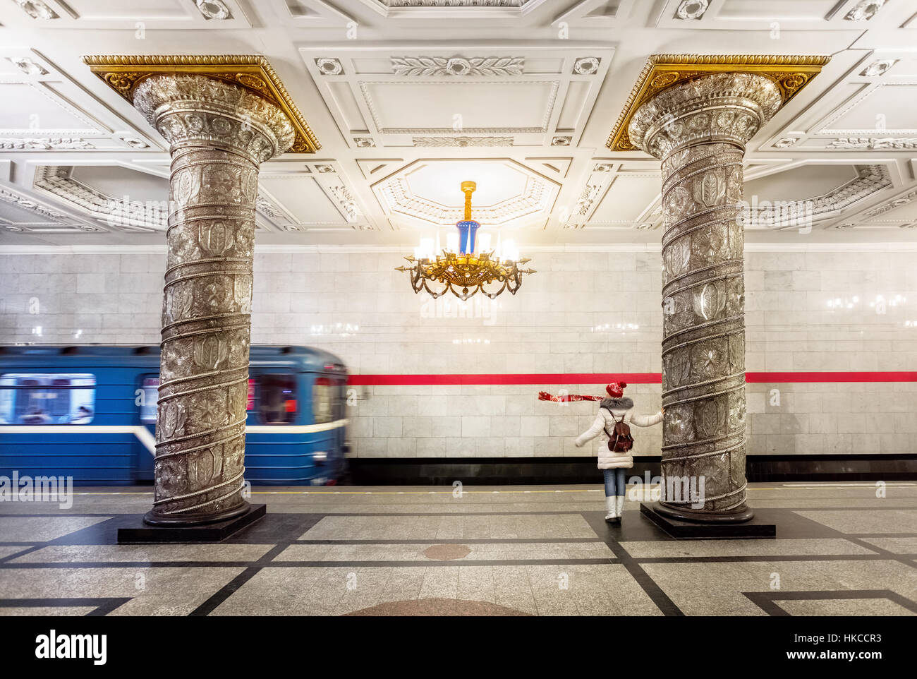 Tourist woman with red scarf and train leaving station in subway Avtovo in Saint Petersburg, Russia - Stock Image
