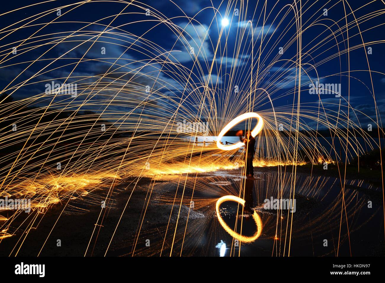 A long exposure of steel wool spinning on a with sparks reflected in a lake Stock Photo