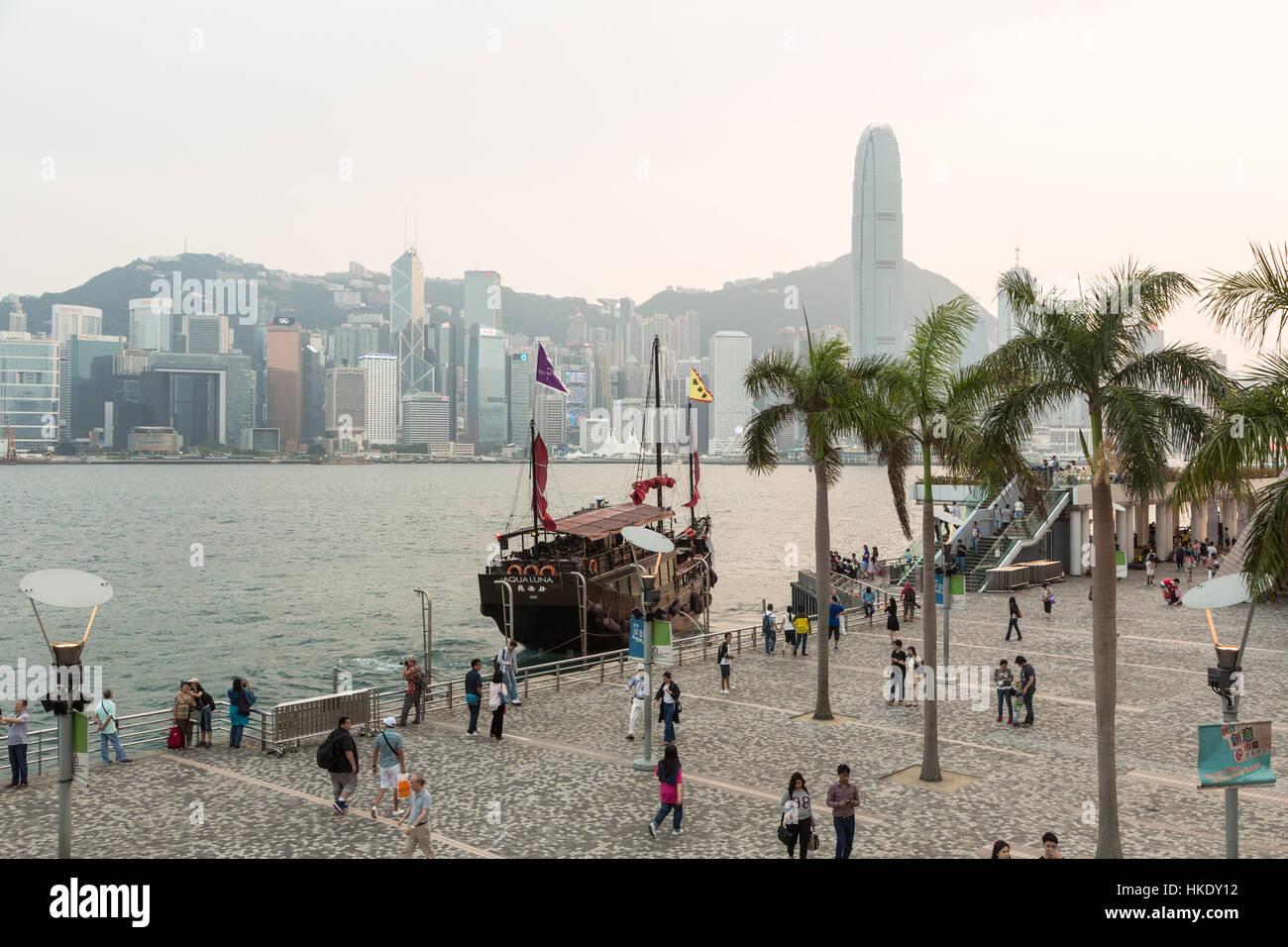 Hong Kong, Hong Kong - April 26 2015: Tourists take pictures and enjoy the famous Hong Kong island skyline across Stock Photo