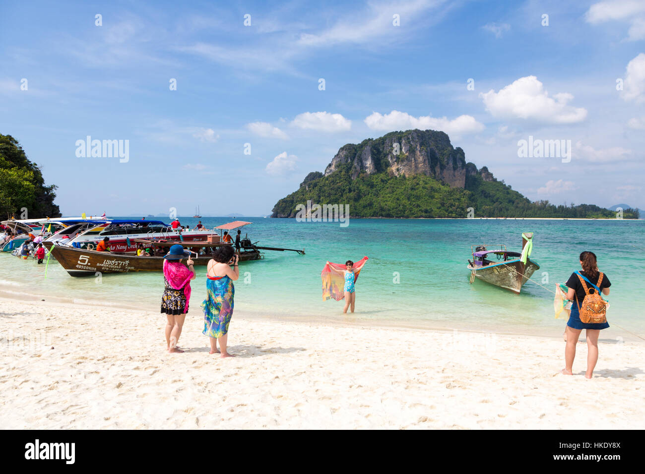 KRABI, THAILAND - DECEMBER 19 2015: Two Chinese tourists take a photo of their friend in front of an island near - Stock Image