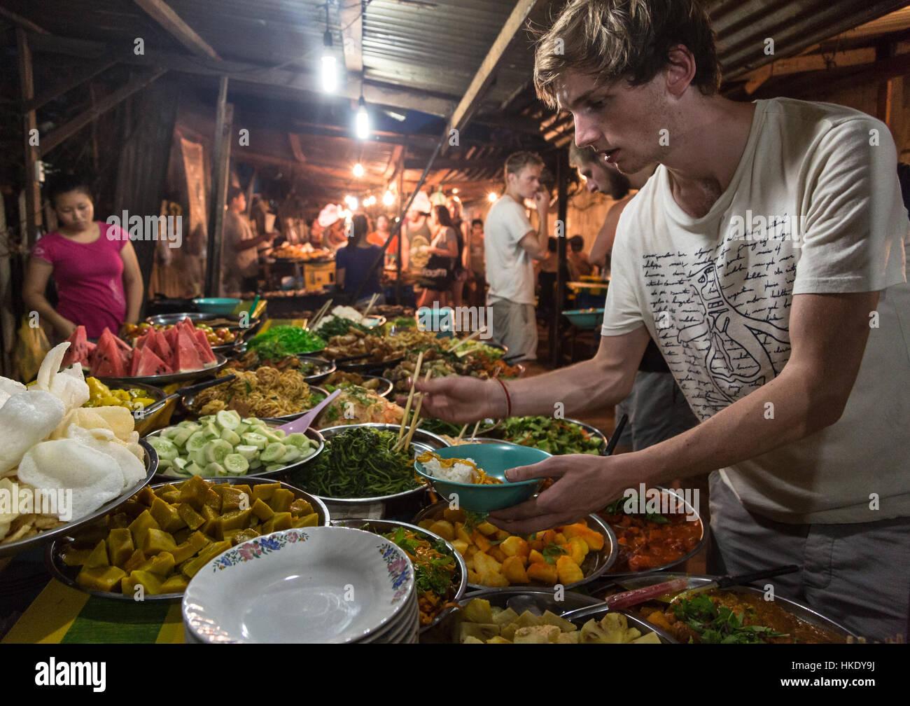 LUANG PRABANG, LAOS - MAY 15 2015: A young caucasian tourist buys food from a market stall in Luang Prabang night - Stock Image