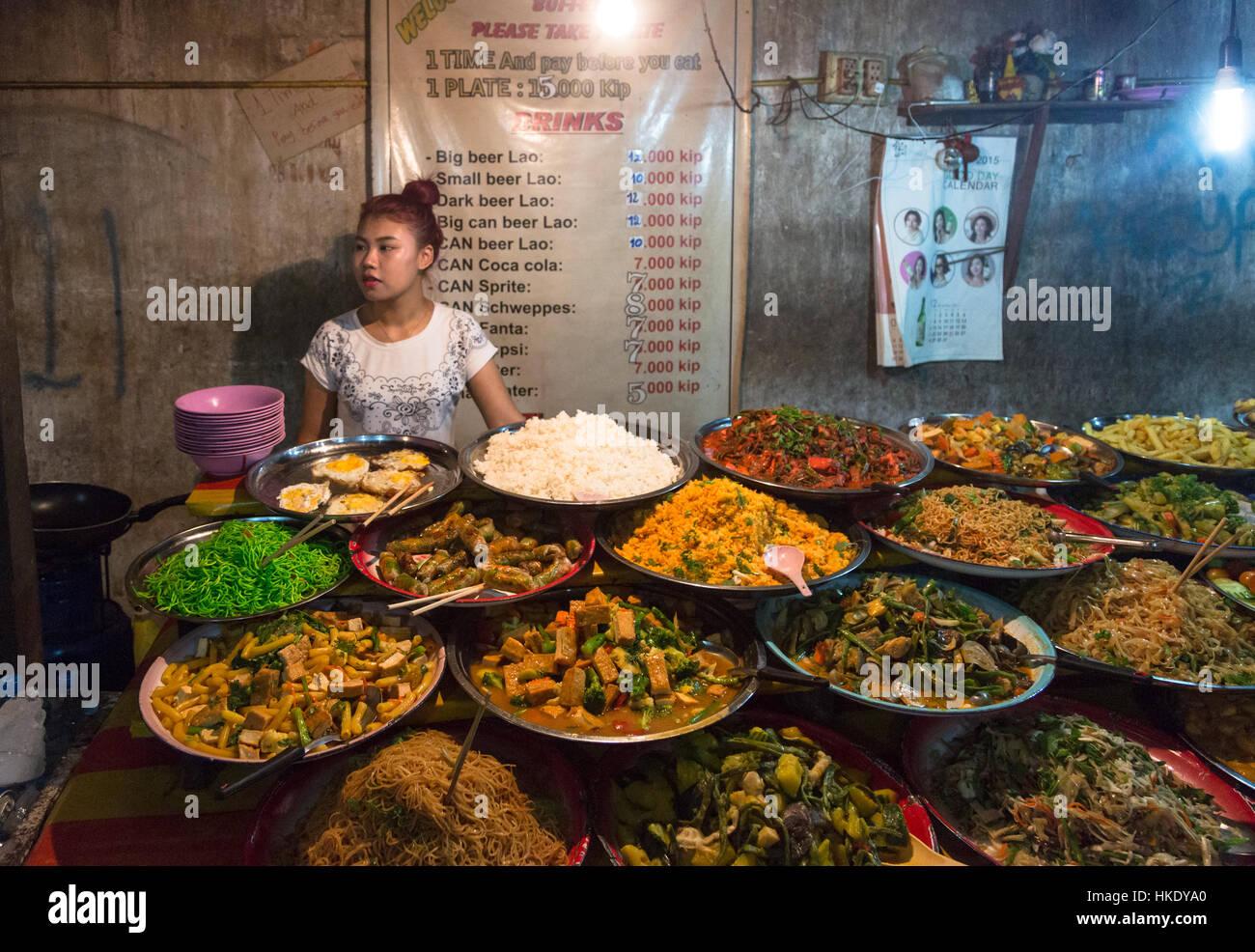LUANG PRABANG, LAOS - MAY 15 2015: A young Laotian woman sells food to tourists in a market stall in Luang Prabang - Stock Image