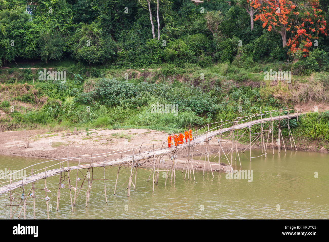 LUANG PRABANG, LAOS - MAY 16 2015: Buddhist monks cross a wooden bridge on the Nam Ou river in Luang Prabang in - Stock Image