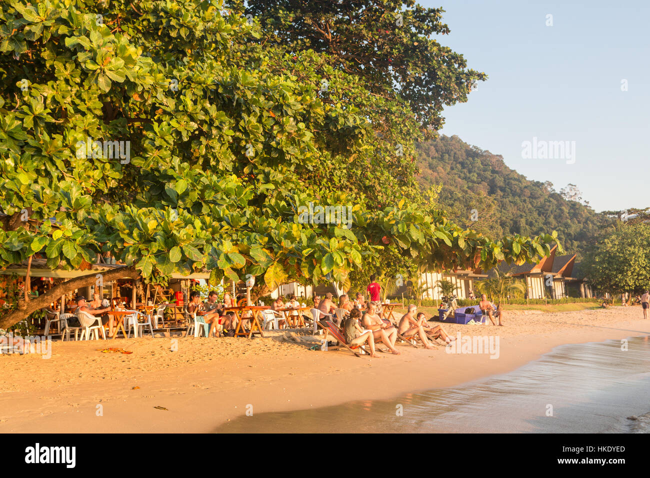 KOH CHANG, THAILAND - DECEMBER 29, 2015: Tourists enjoy a drink in a beach bar during sunset over white sand beach Stock Photo