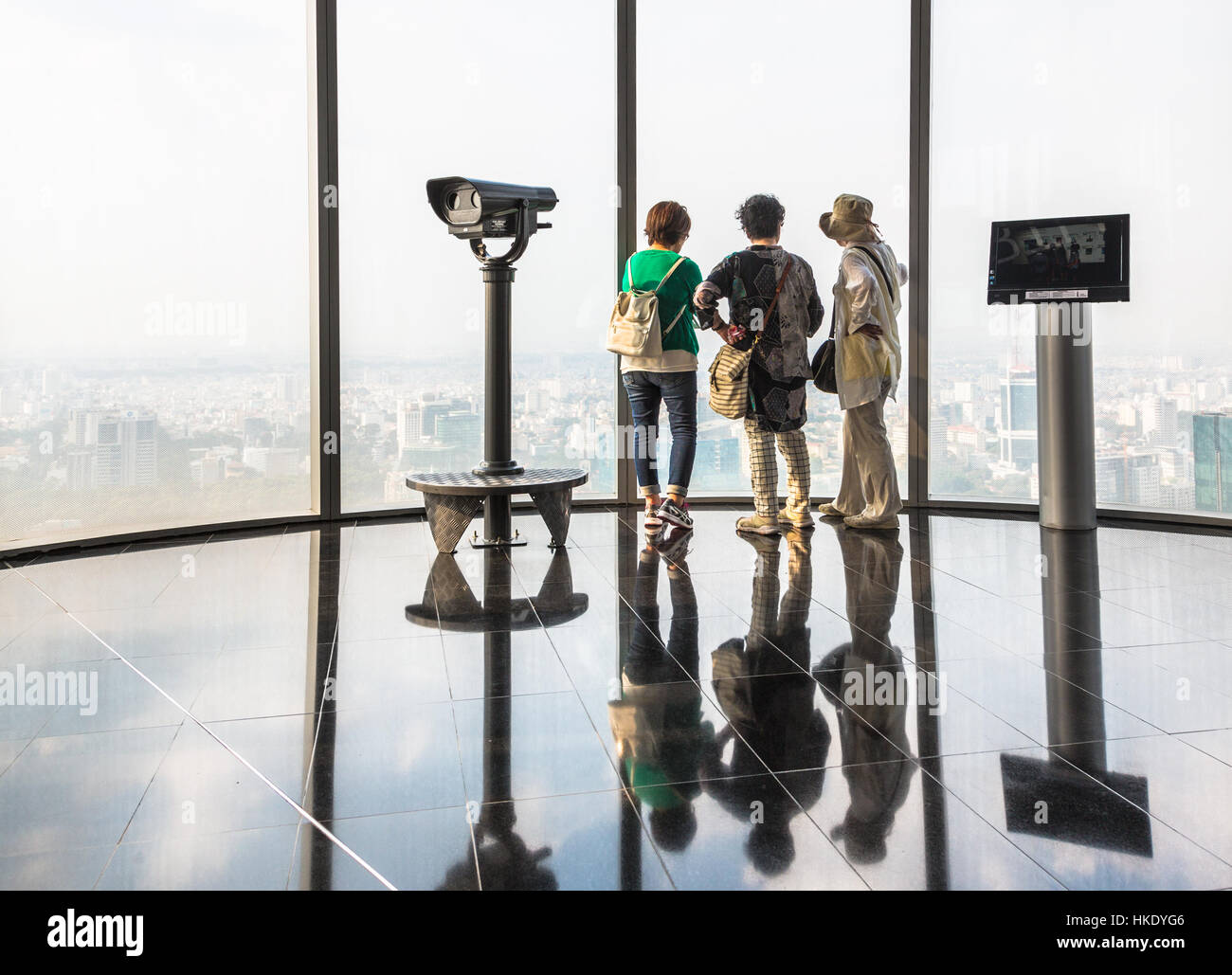 HO CHI MINH CITY, VIETNAM - FEBRUARY 2, 2016: 3 Asian female tourists enjoy the view over Ho Chi Minh City from - Stock Image