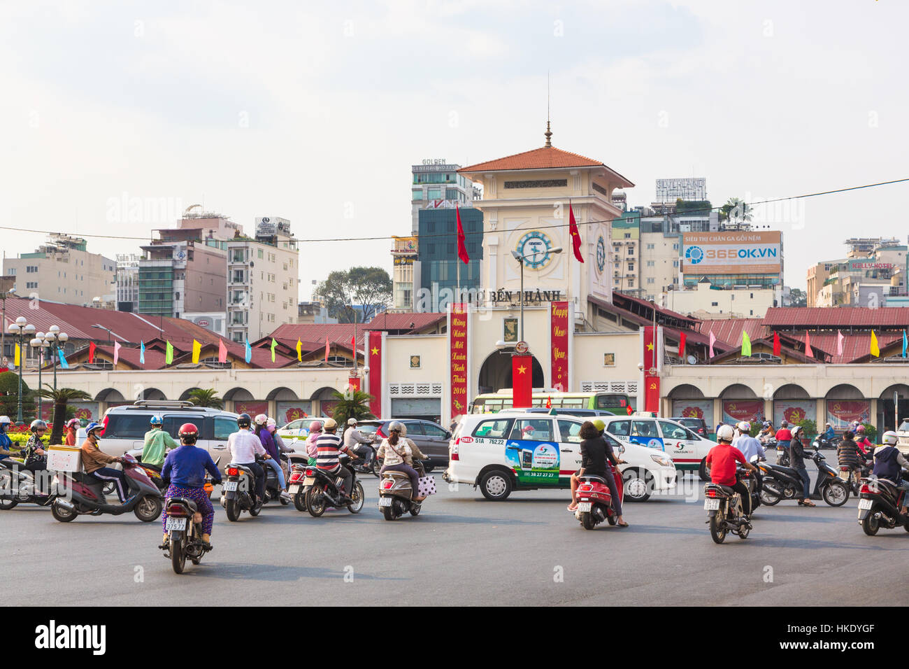 HO CHI MINH CITY, VIETNAM - FEBRUARY 2 2016: Cars and motorcycles rush around the Saigon Central Market known locally Stock Photo
