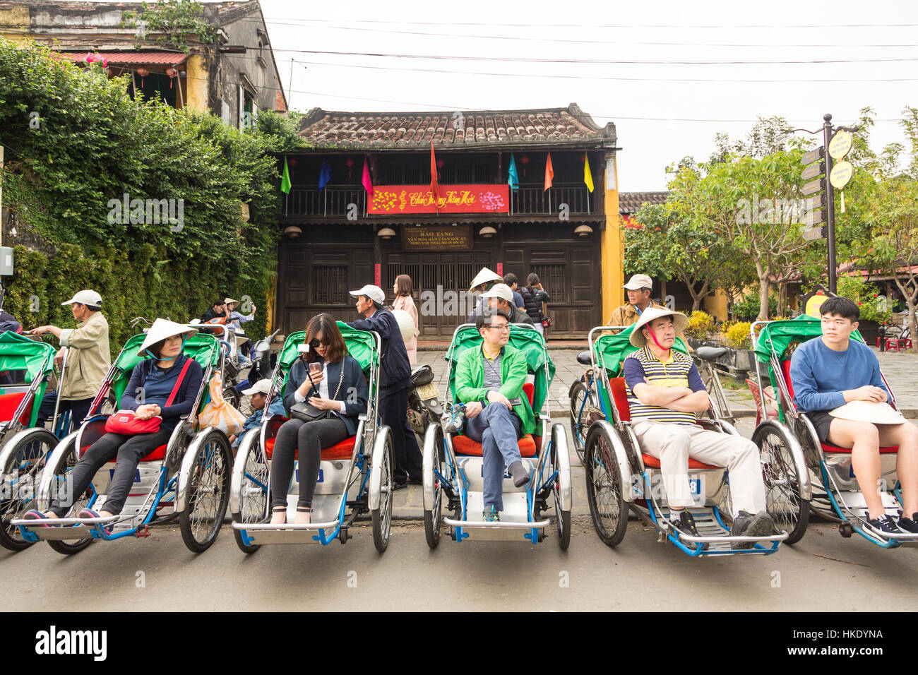 HOI AN, VIETNAM - FEBRUARY 7, 2016: Asian tourists wait for their cyclo tour of Hoi An old town to begin. The city - Stock Image