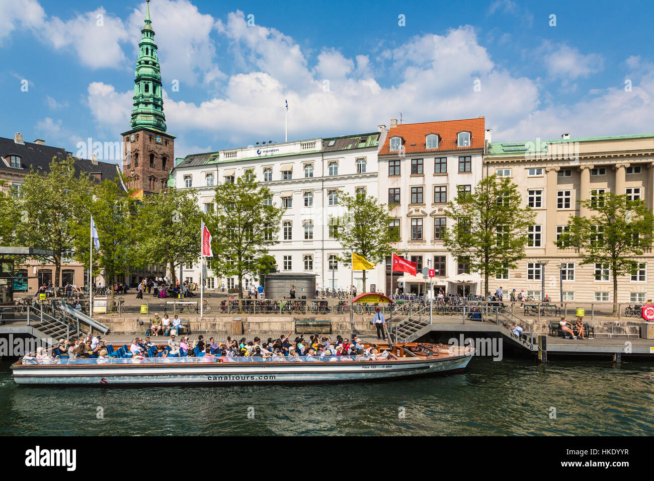 COPENHAGEN, DENMARK - MAY 24, 2016: Tourists enjoy the traditional architecture from a tourist boat along the canals Stock Photo