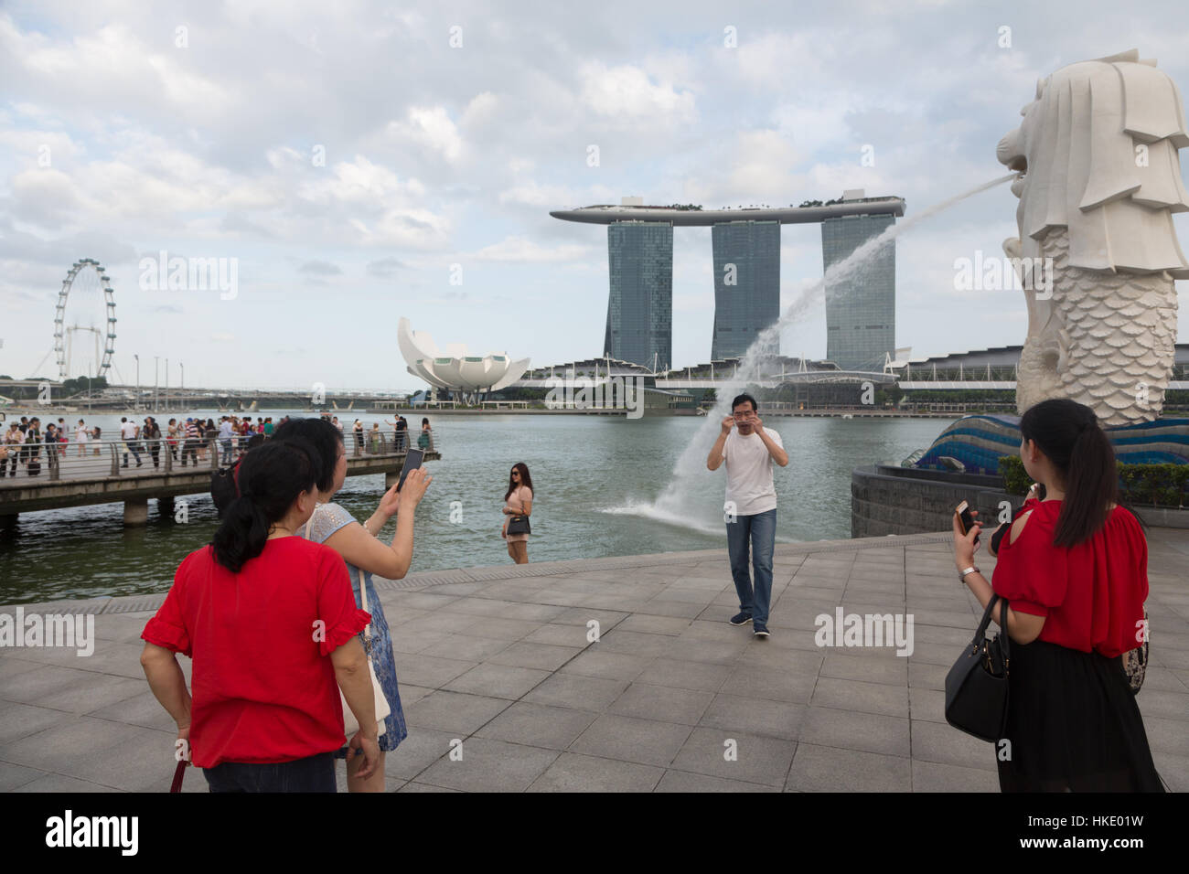 SINGAPORE, SINGAPORE - FEBRUARY 22 2016: Tourists take photo in front of the Marina Sands building and the Merlion - Stock Image