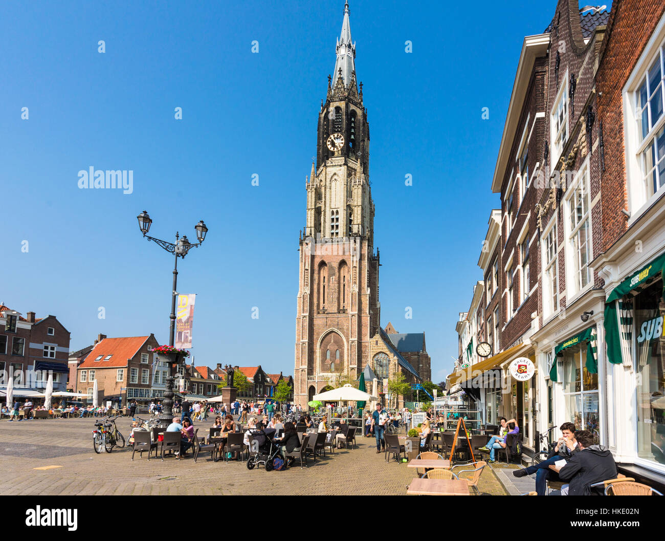 DELFT, THE NETHERLANDS - MAY 28, 2016: People enjoy a coffee on Delft old town main square in front of the tall - Stock Image