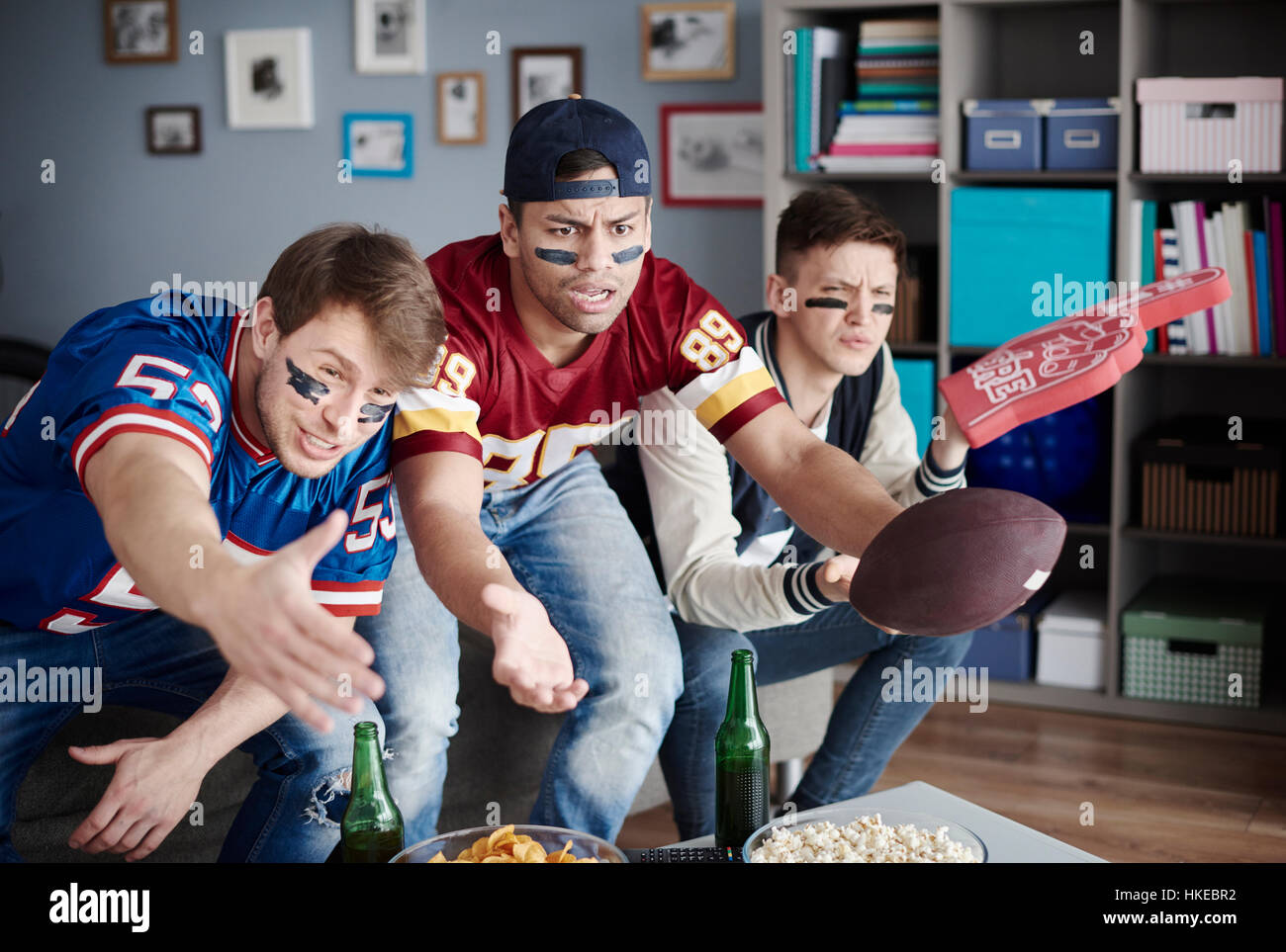 Unhappy men while watching American football - Stock Image