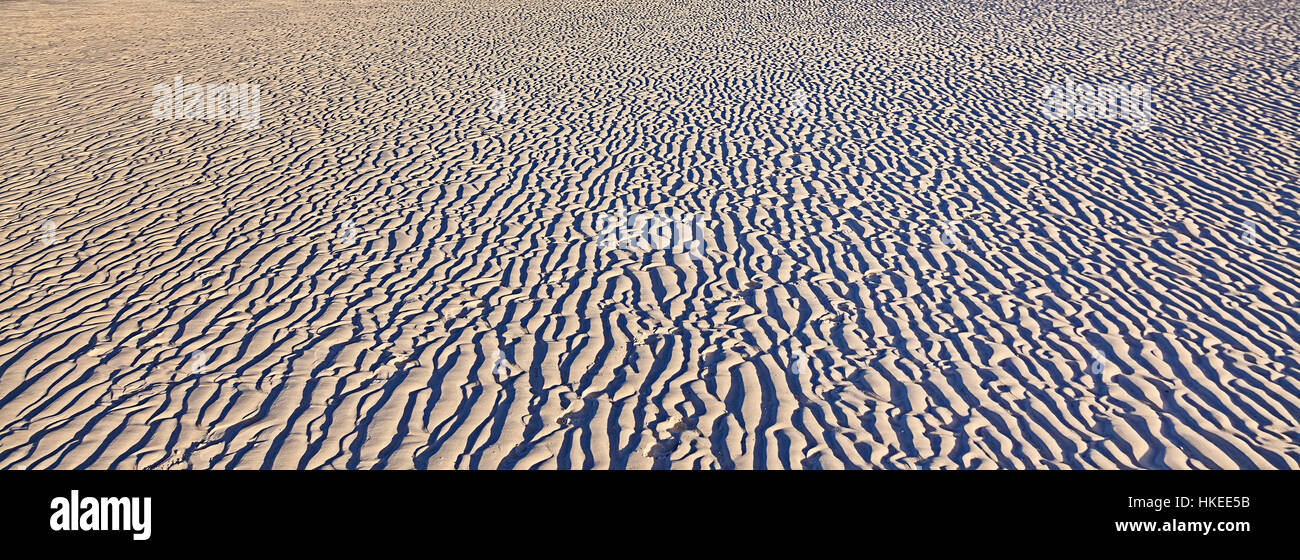 Random light-shade pattern on white silica sandy Whitehaven beach of Whitsundays island formed in wind work traces - Stock Image