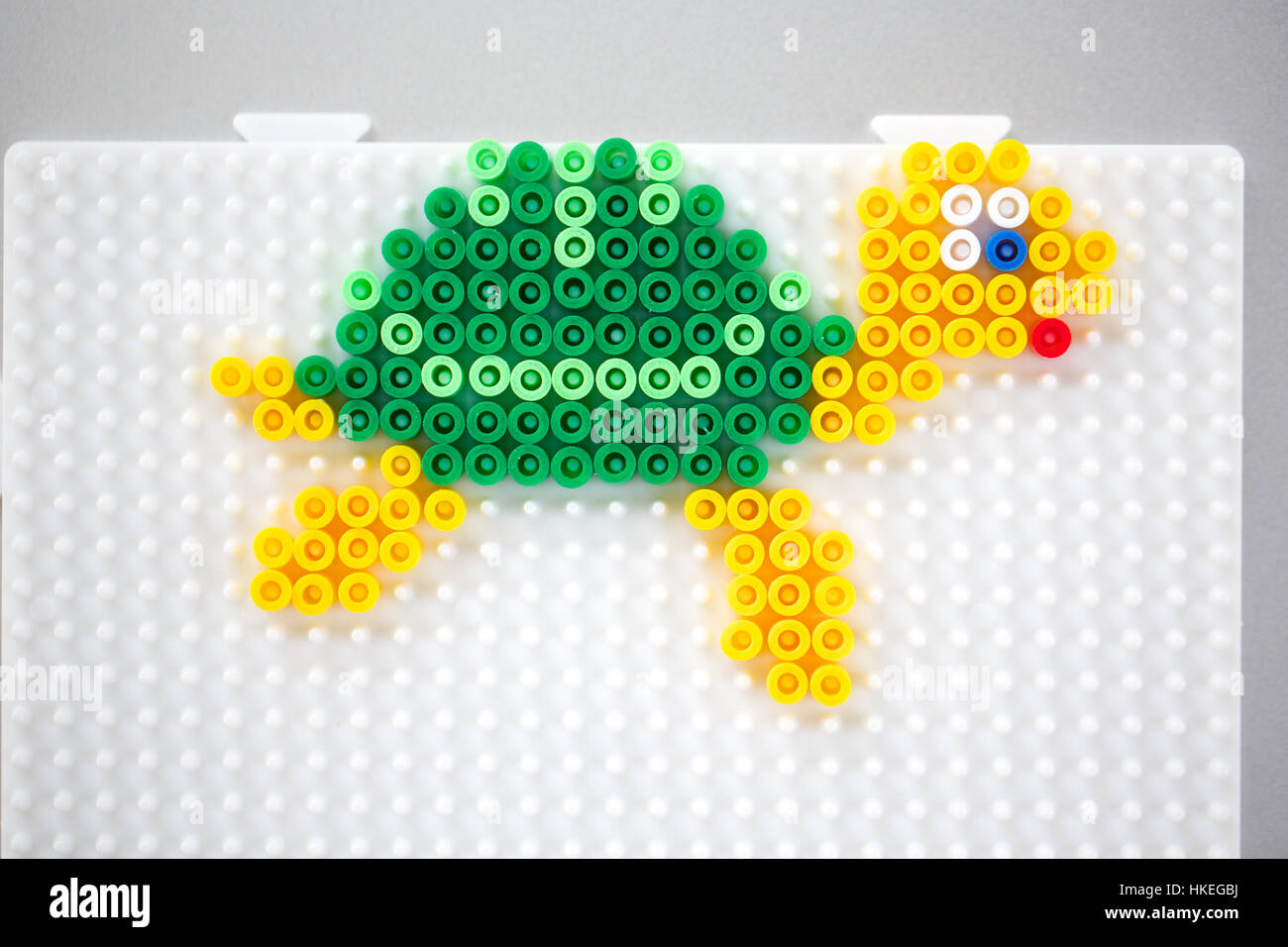 turtle made of fusible beads on pegboard. beads craft, design, toy animal, plastic. - Stock Image