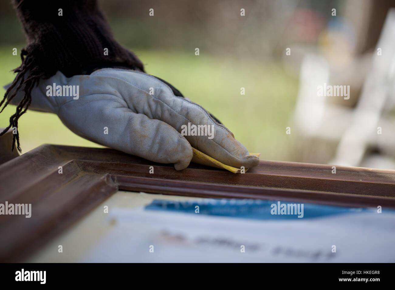 carpenter sanding wooden surface. sand paper, glove, working, wood. - Stock Image