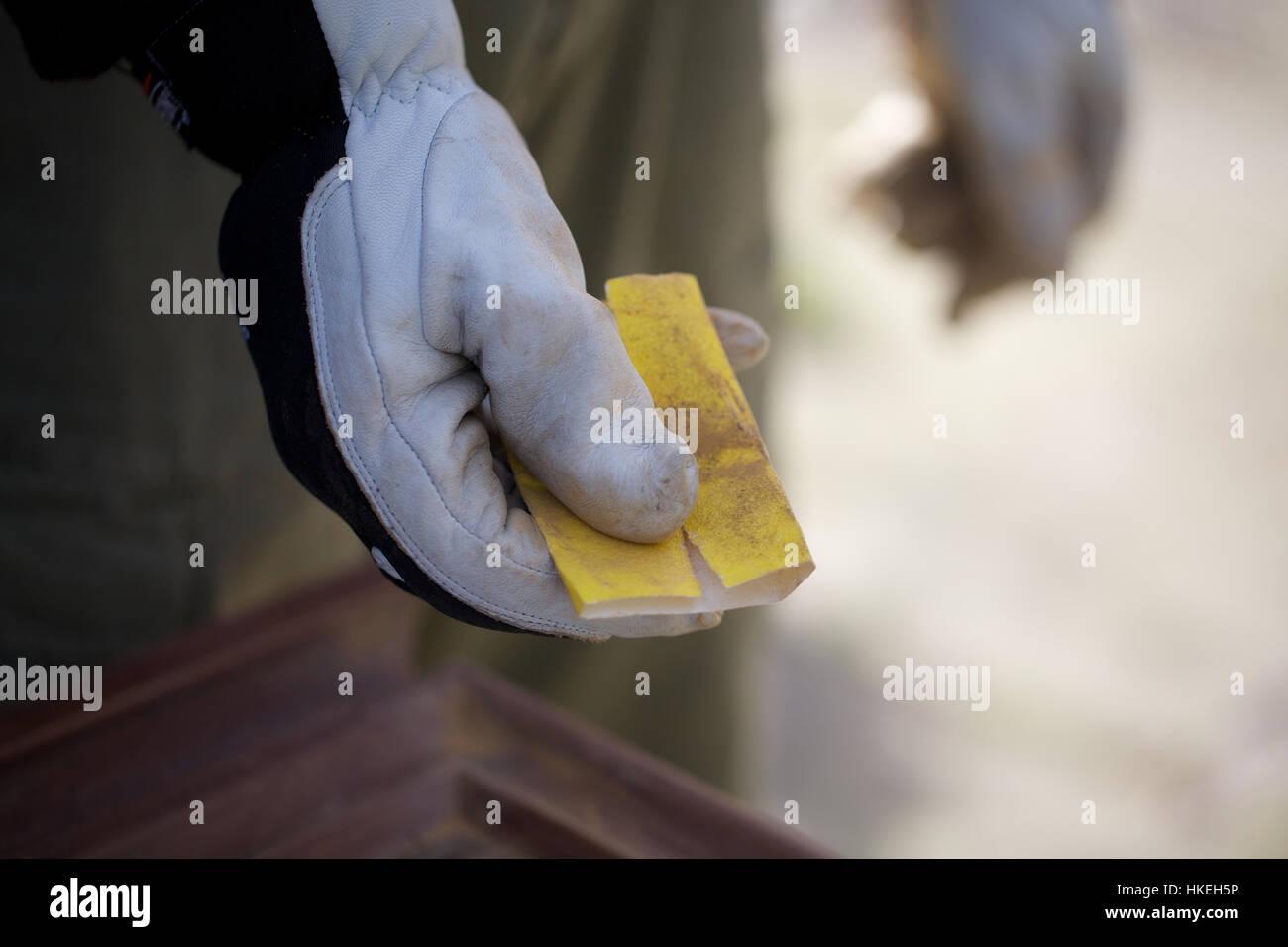 carpenter holding sandpaper. hand, glove, worker, sand paper. - Stock Image