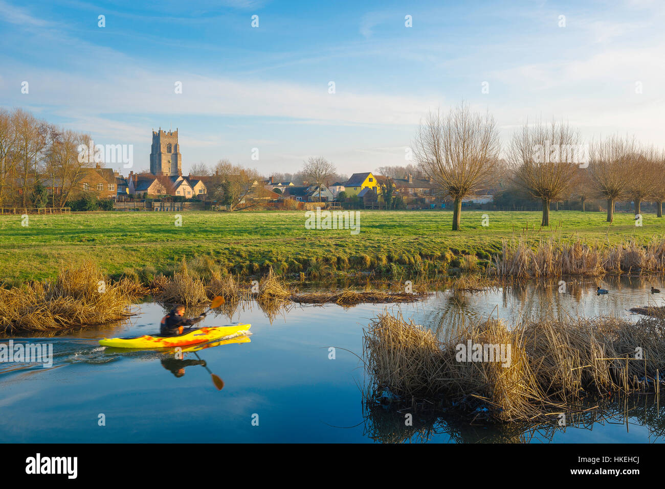 A man paddles his yellow canoe on the River Stour in winter with the Suffolk town of Sudbury in the background, - Stock Image