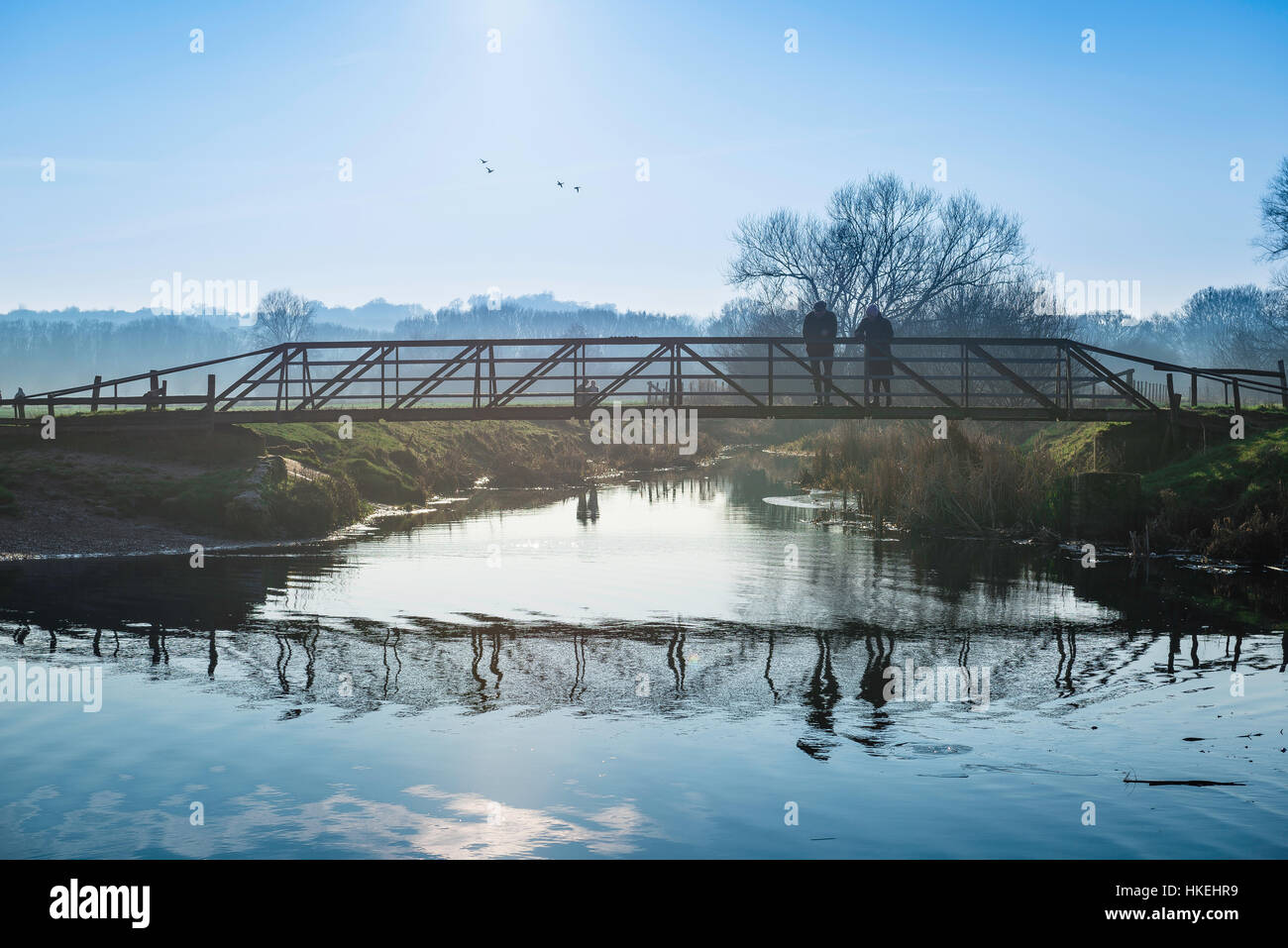 Suffolk landscape, in winter a middle aged couple pause on a bridge to look at the River Stour in a water meadow - Stock Image