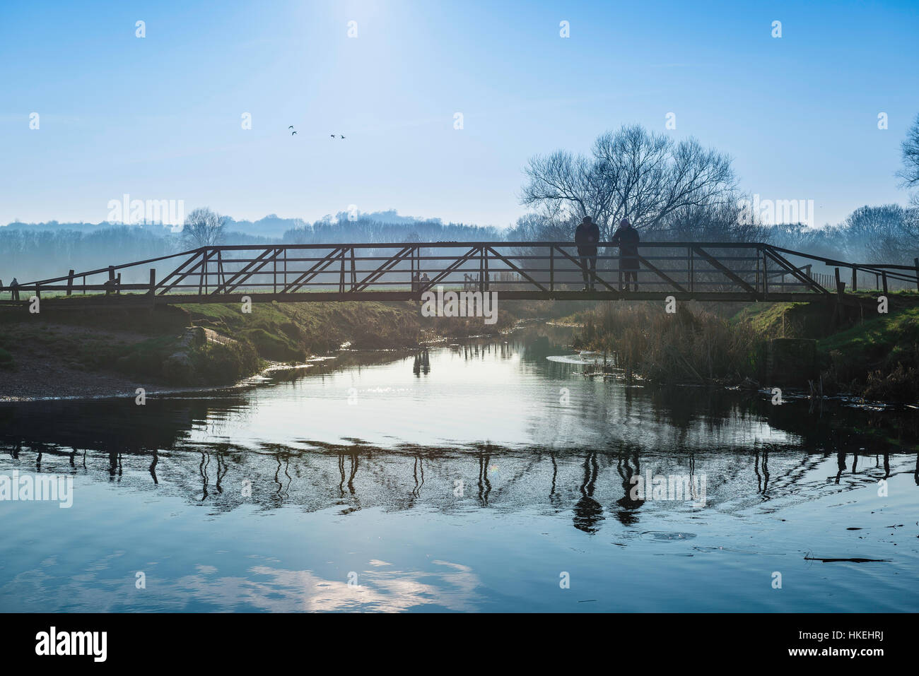 Sudbury Suffolk, a couple chat on a bridge over the River Stour in the water meadows at winter-time in Sudbury, - Stock Image