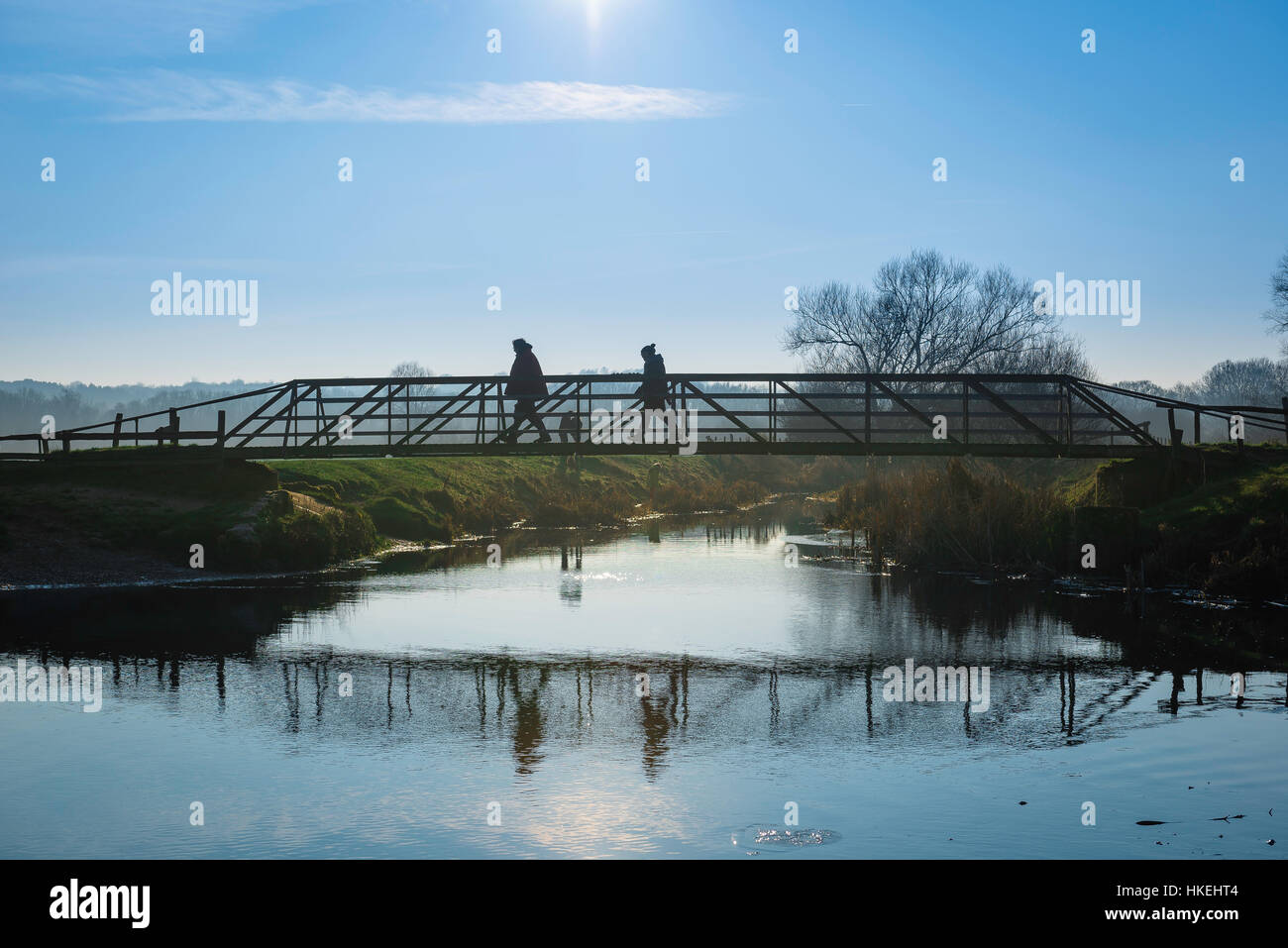 A middle aged couple taking a winter walk cross a bridge over the River Stour in Suffolk, UK. - Stock Image