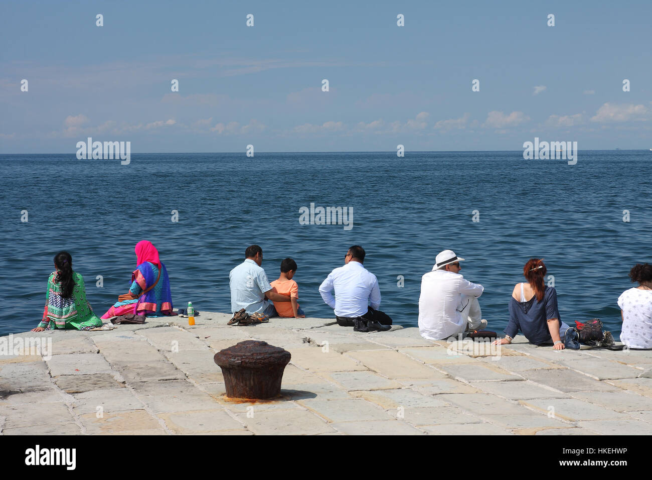 TRIESTE, ITALY - AUGUST 18, 2015: Group of turists  seats on Molo Audace on August 18, 2015 in Trieste on Italy. Trieste is a popular tourist town in  Stock Photo