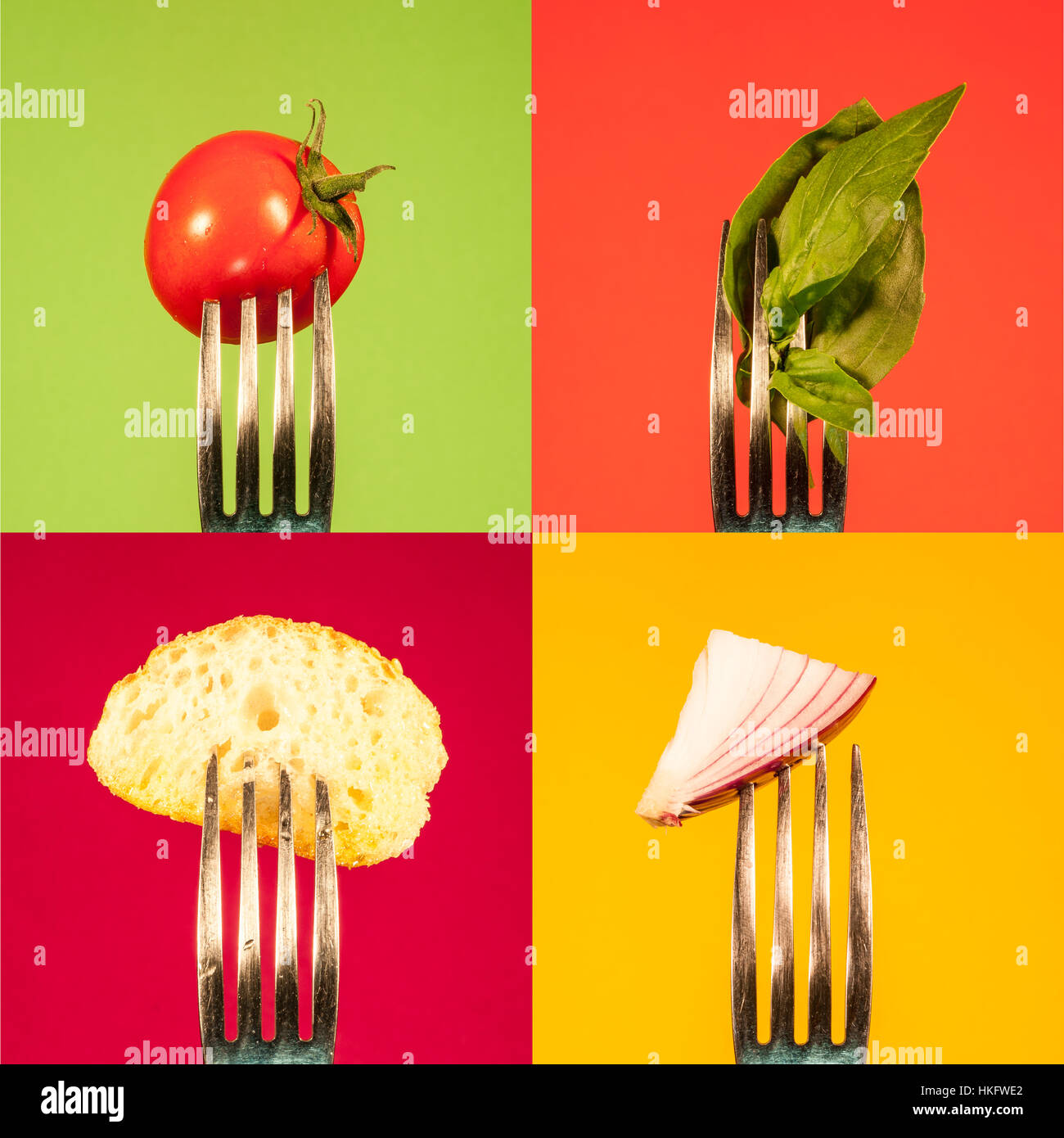 Tomato onion basil bread on forks arranged in squares on colourful background - Stock Image