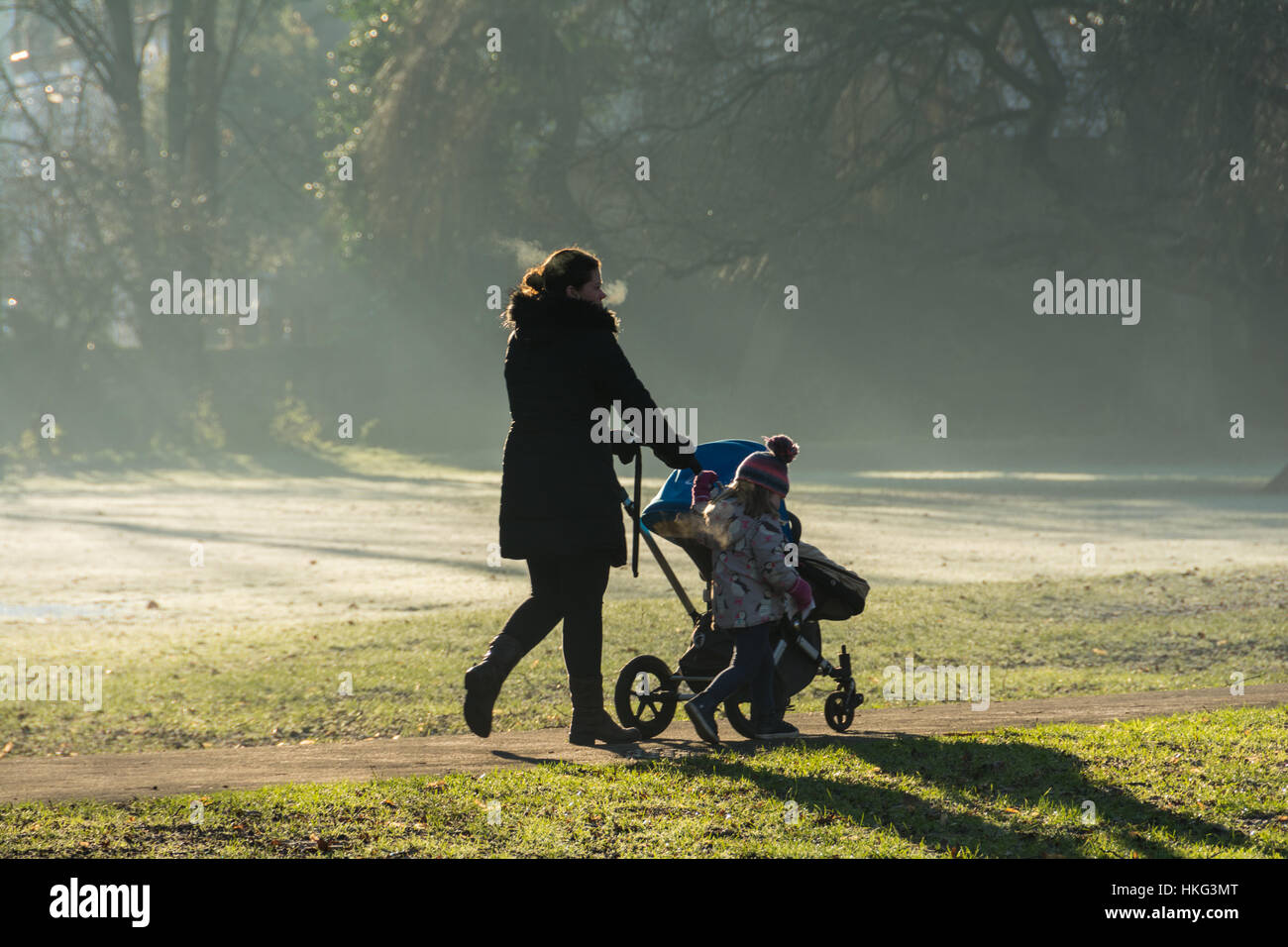 A Mum walking her children to nursery school on a frosty morning. - Stock Image