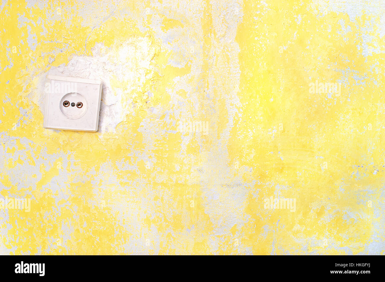 Wall socket on the yellow old plastered wall whith copyspace. Old electrical outlet on a decrepit wall. Fragment Stock Photo