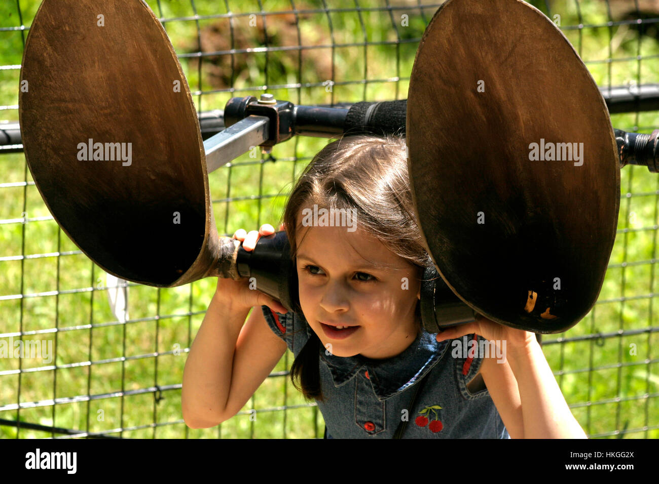 Little girl having fun with large ears on at the ZOO - Stock Image