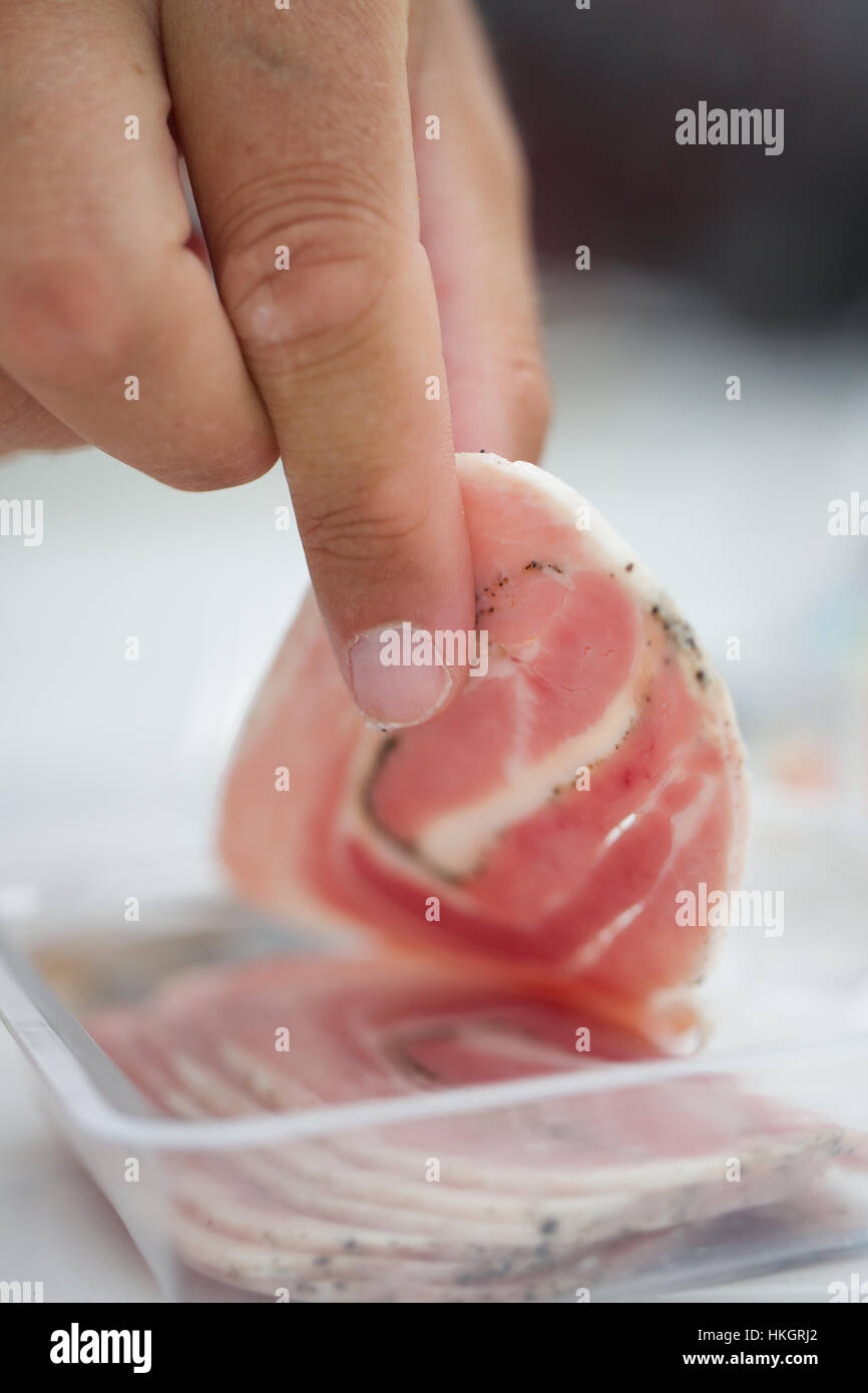 slices of rolled meat sausage. pork roll, seasoned, hand, food. Stock Photo