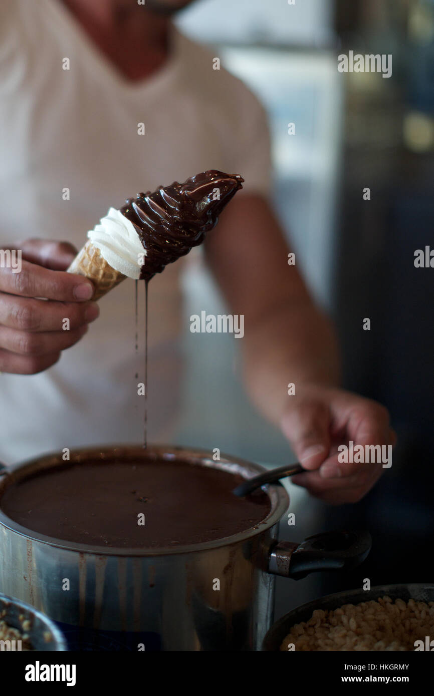 man holding softice cone with chocolate spilling. container, ice cream, unhealthy, food. - Stock Image