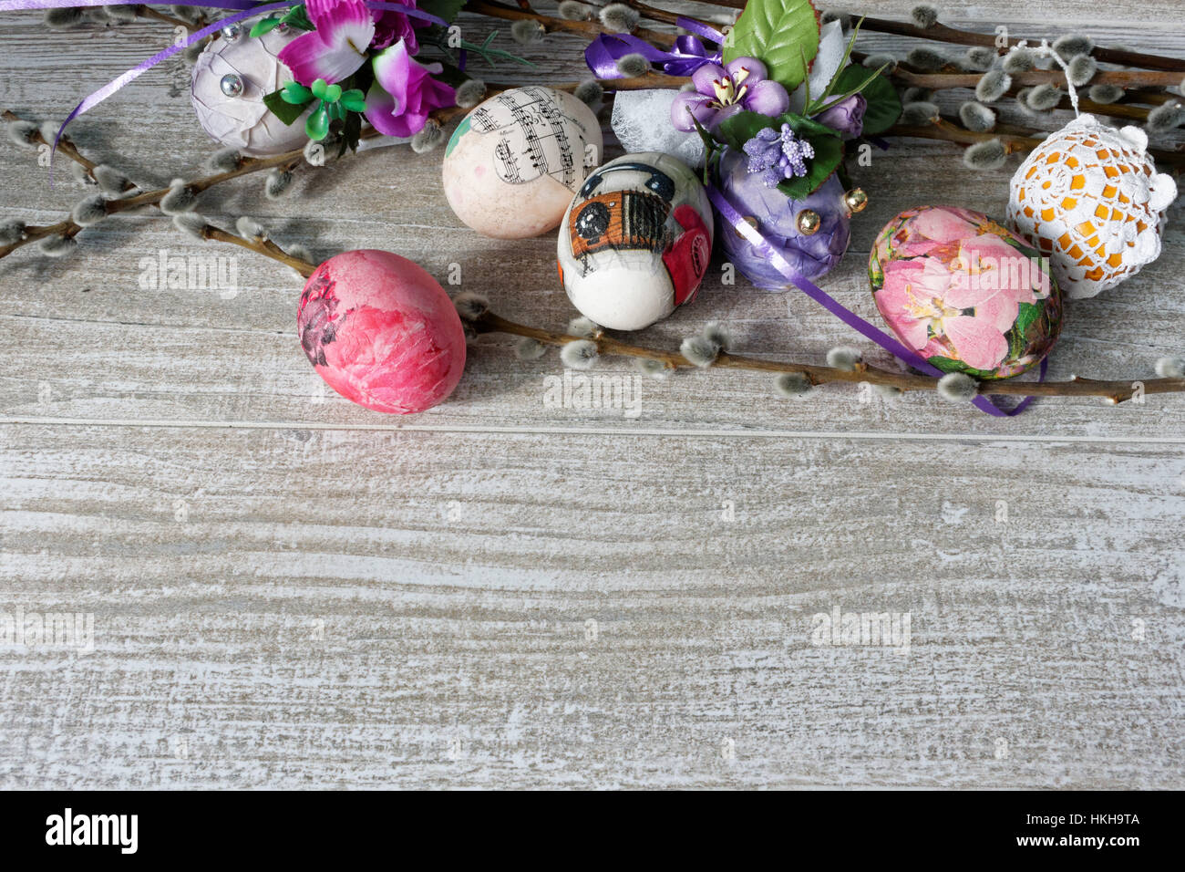 Decoupage decorated colorful Easter eggs with willow branches on wooden table Stock Photo