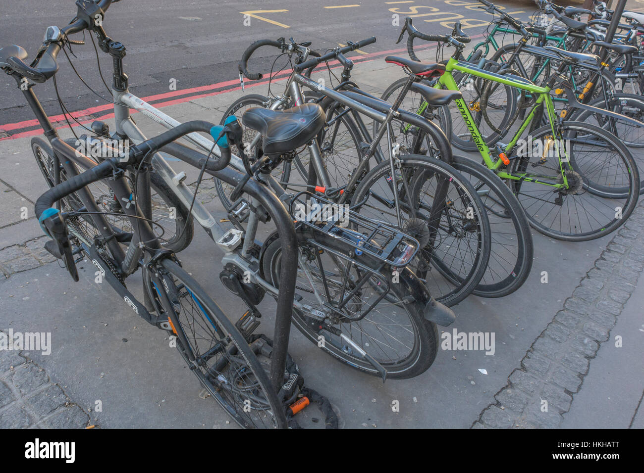 Cycle rack / rank in City of London financial district. Focus on forward bikes. Metaphor for getting around London, - Stock Image