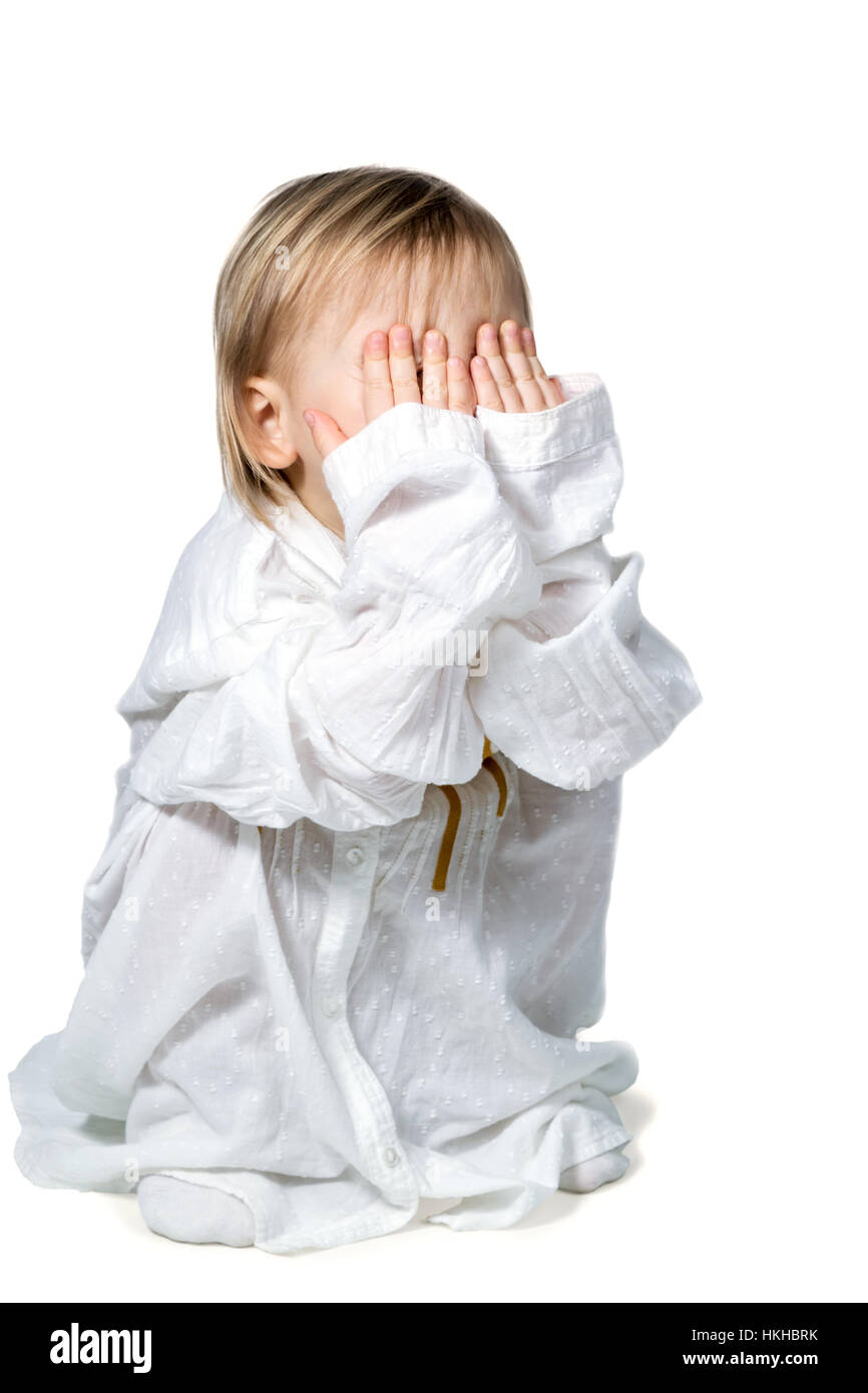 Small child playing hide and seek - Stock Image