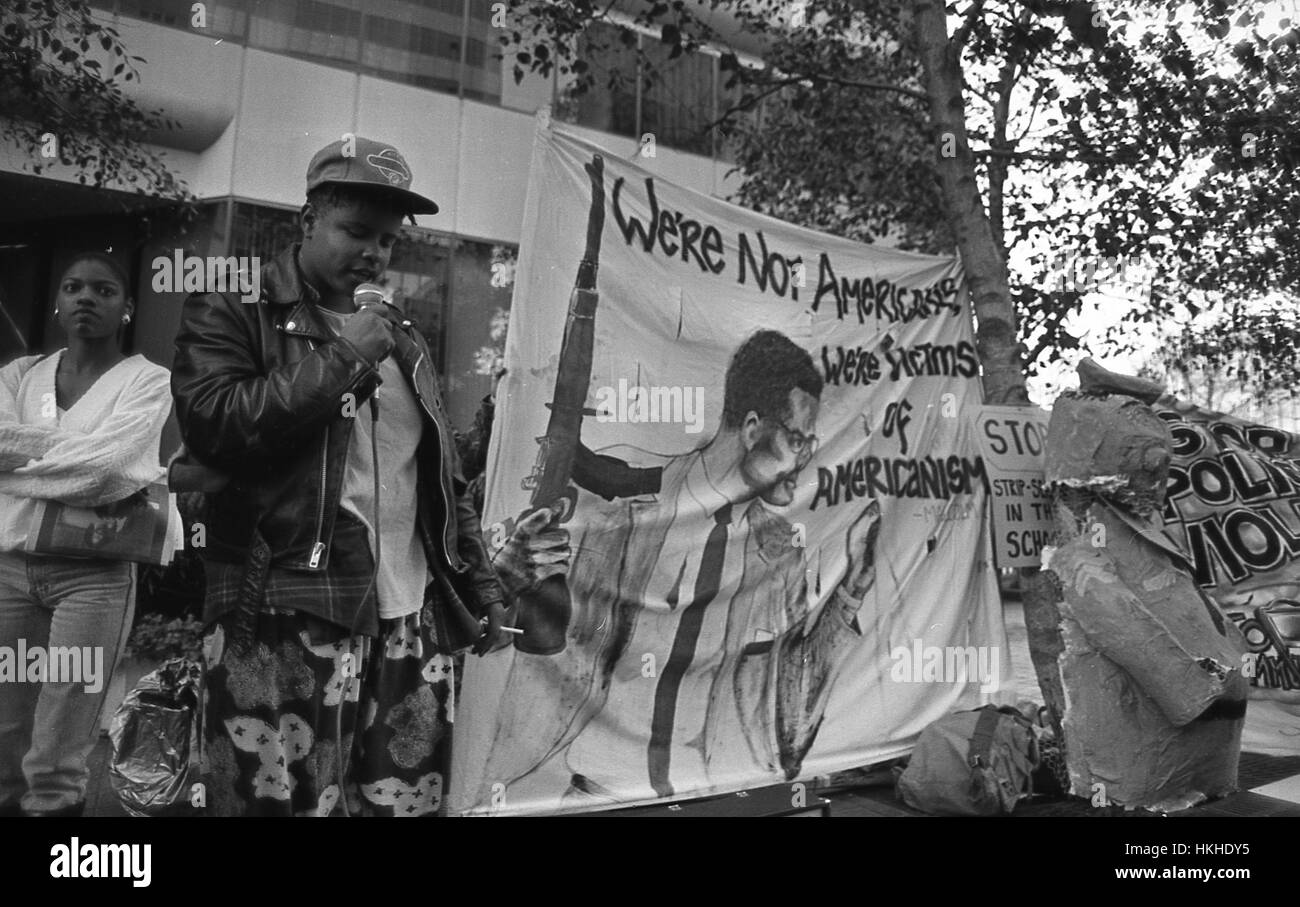 African-American protester speaking on a portable public address system, other holding a banner showing Malcolm - Stock Image
