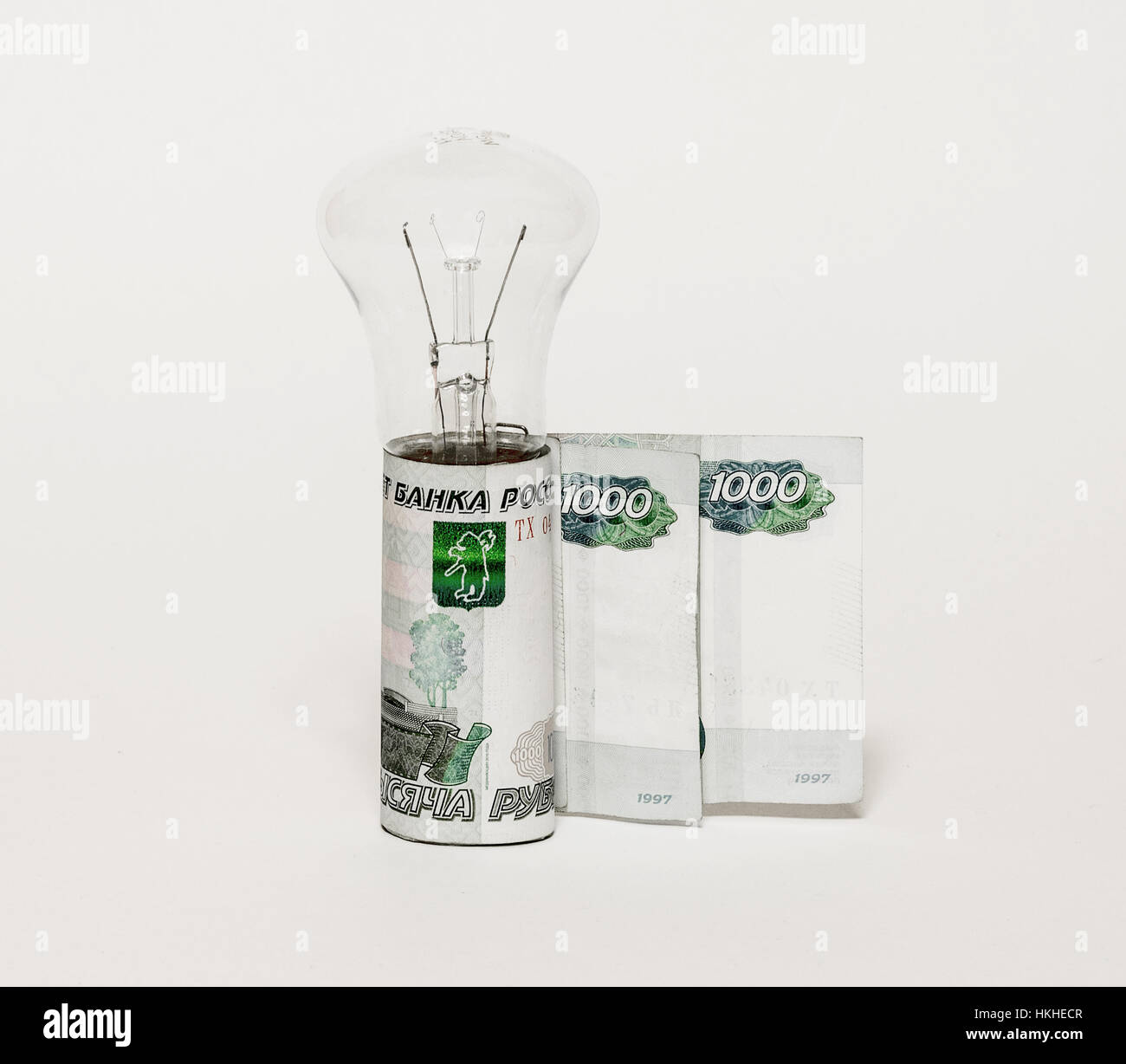Incandescent electric lamp and money bills Stock Photo