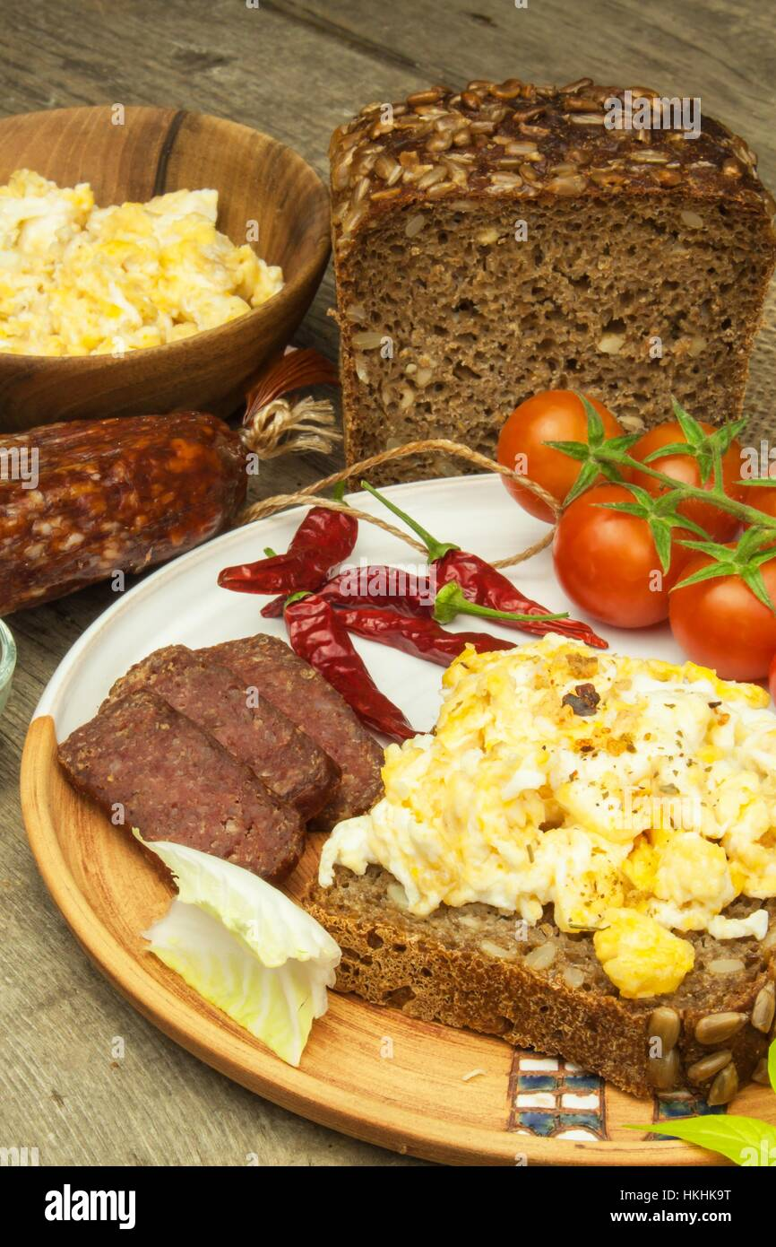 Scrambled eggs with bread and salami. Egg breakfast on a wooden table. Healthy food. Stock Photo