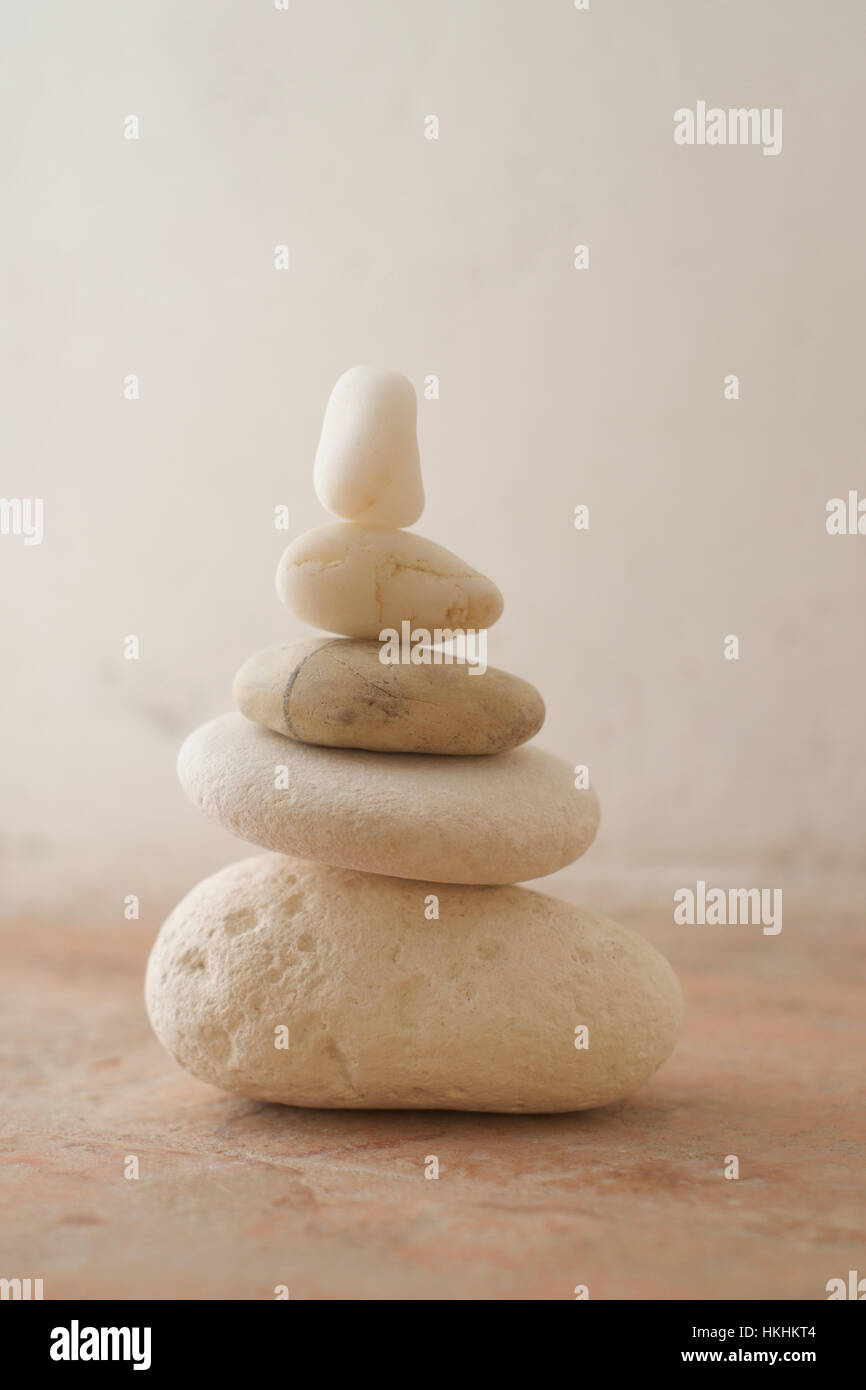 A stack of pebbles with light tones against a rustic background - Stock Image