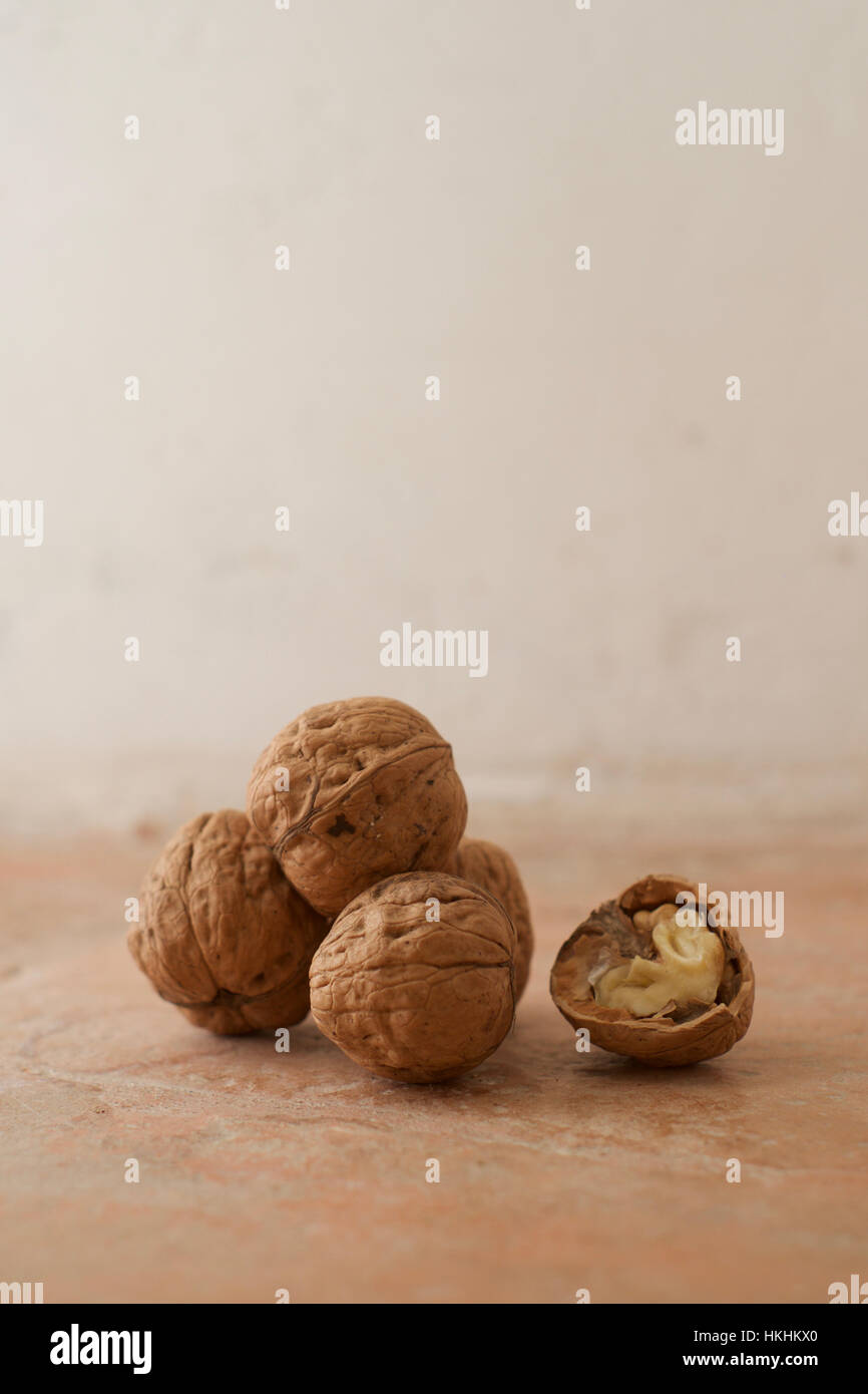 A stack of four whole walnuts with one half walnut showing the nut inside - Stock Image