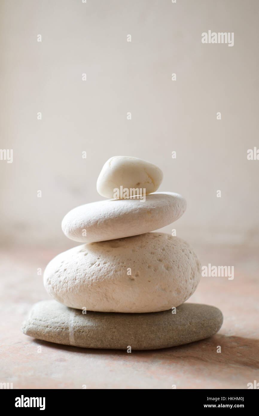 A stack of pebbles with white tones against a rustic background - Stock Image