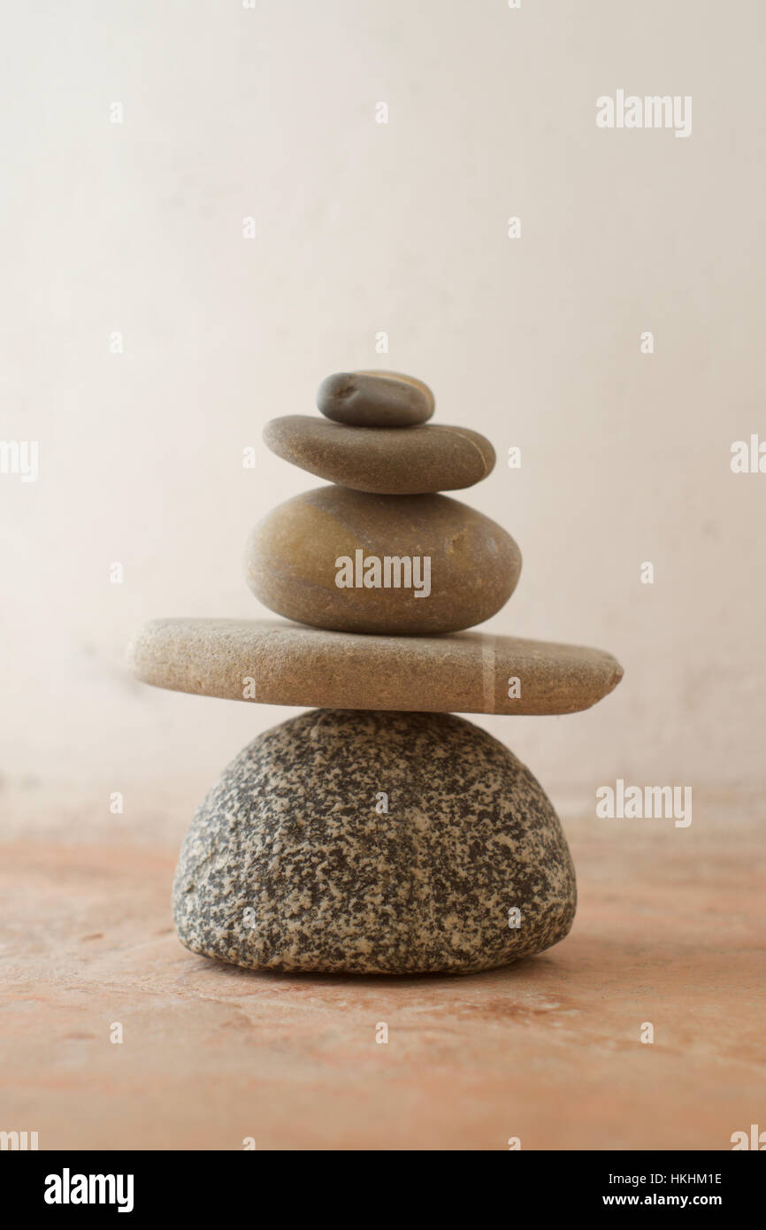 A stack of pebbles with grey tones against a rustic background - Stock Image