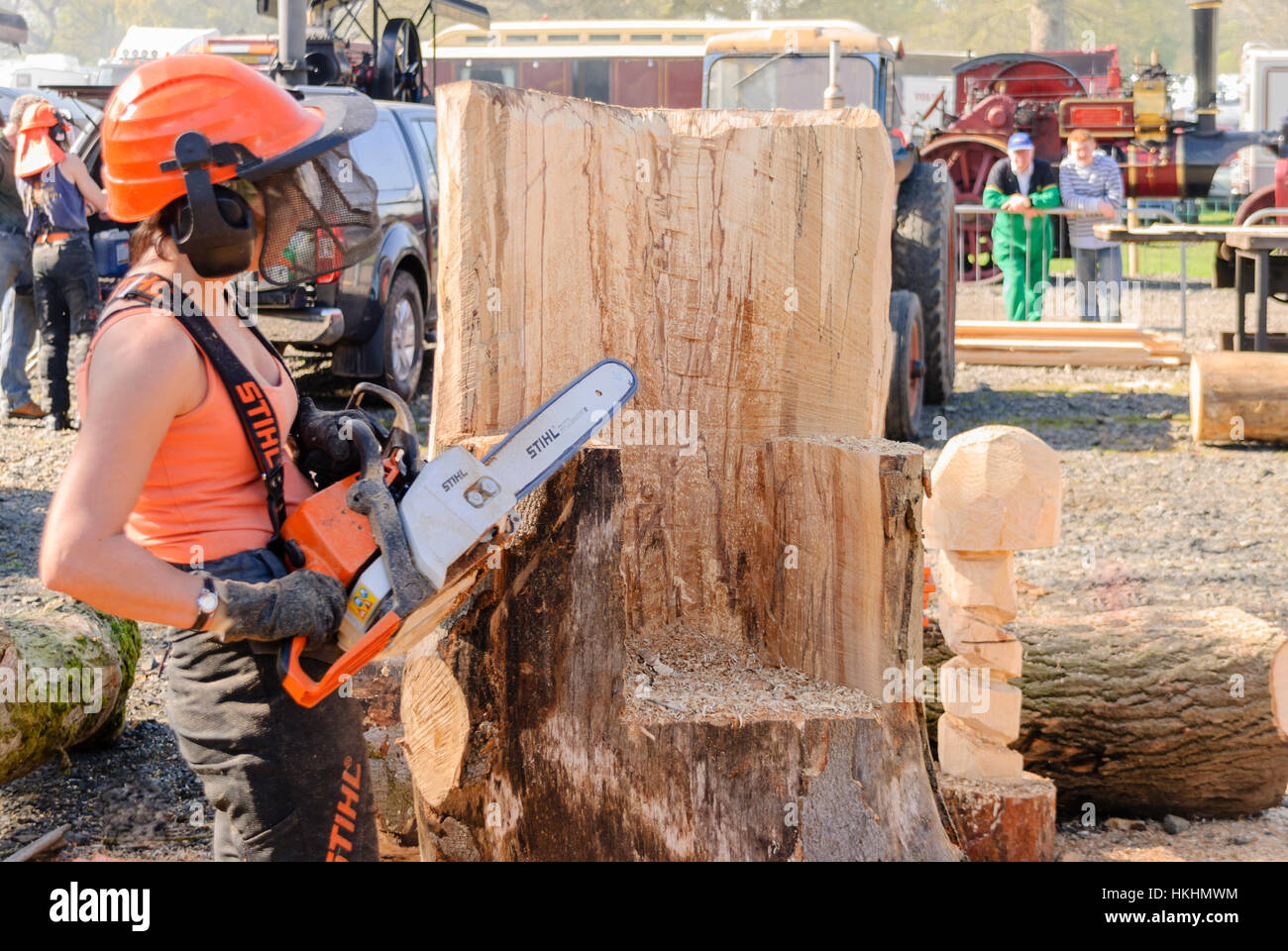 Woman Uses A Stihl Chainsaw To Carve A Tree Trunk Into A
