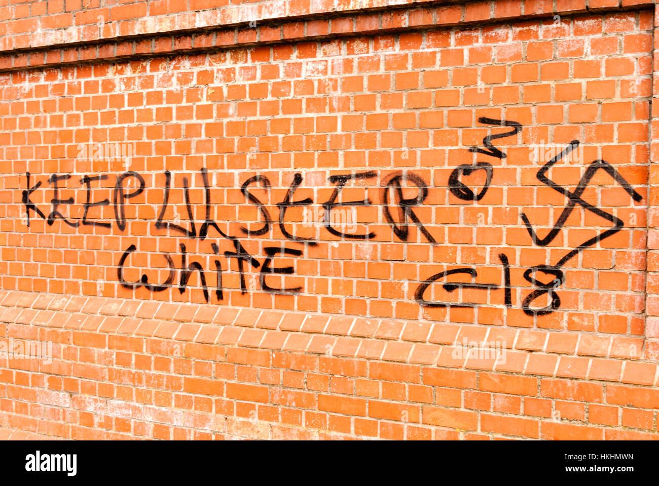 Graffiti on a brick wall saying 'Keep Ulster White, C18' (Combat 18_ with a Nazi swastika - Stock Image
