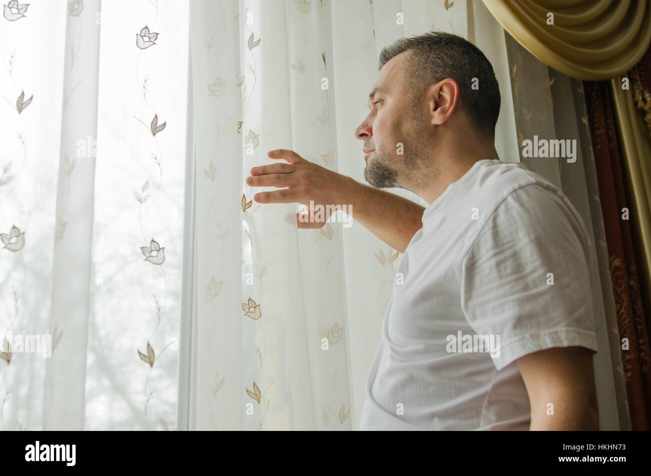 young man looking through a window blind and smiling - Stock Image